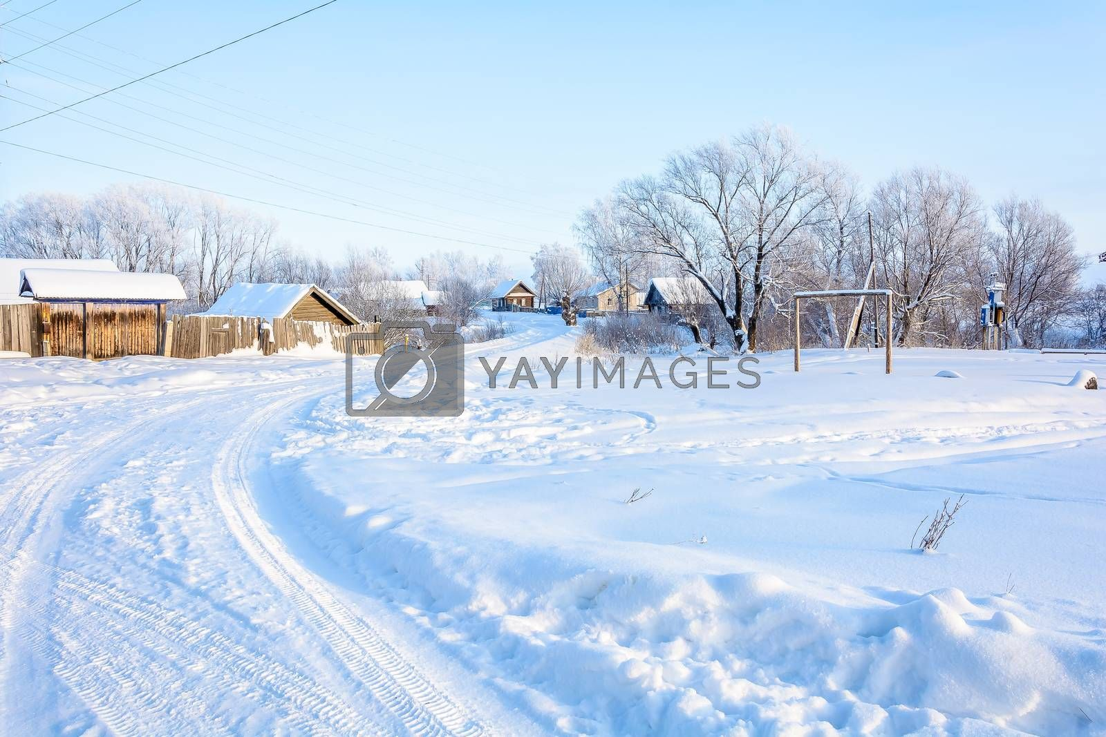 Snowy winter road leading to the village