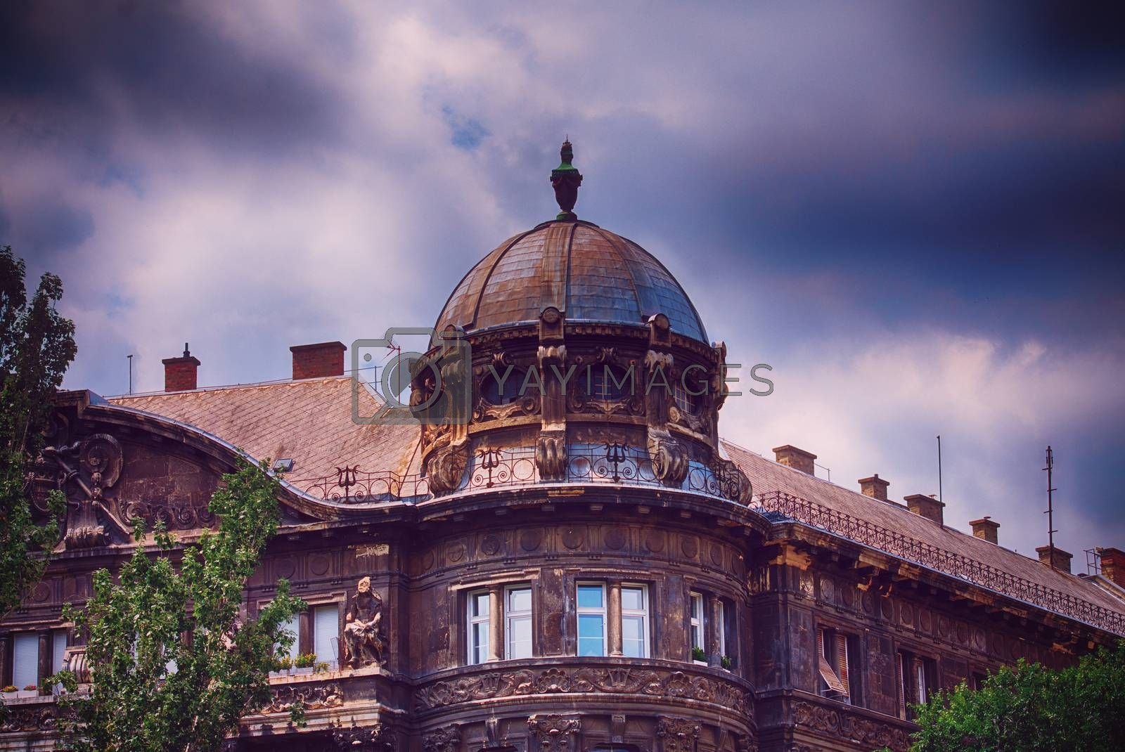 Beautiful domed old building in Budapest with dark blue stormy clouds in the background. The calm before the storm in Budapest.