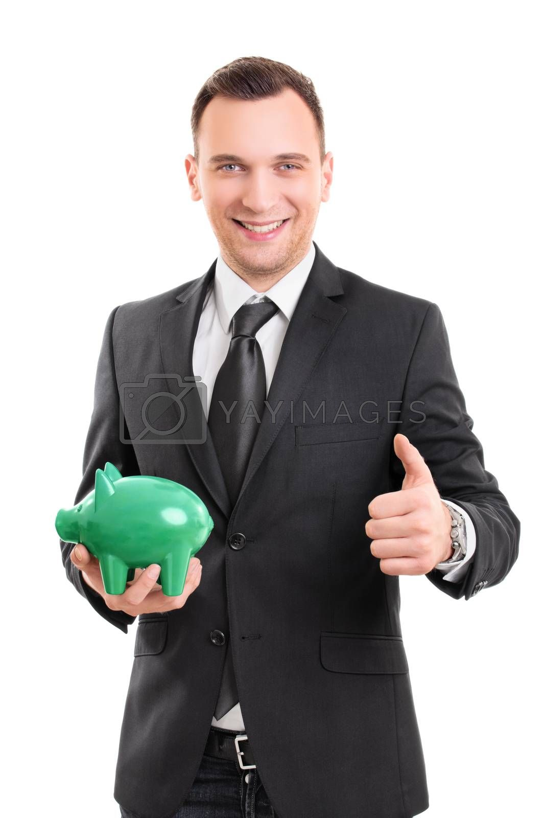Handsome young businessman in a suit holding a piggy bank, smiling and giving thumb up, isolated on white background. Saving money concept. Confident businessman with a piggy bank.