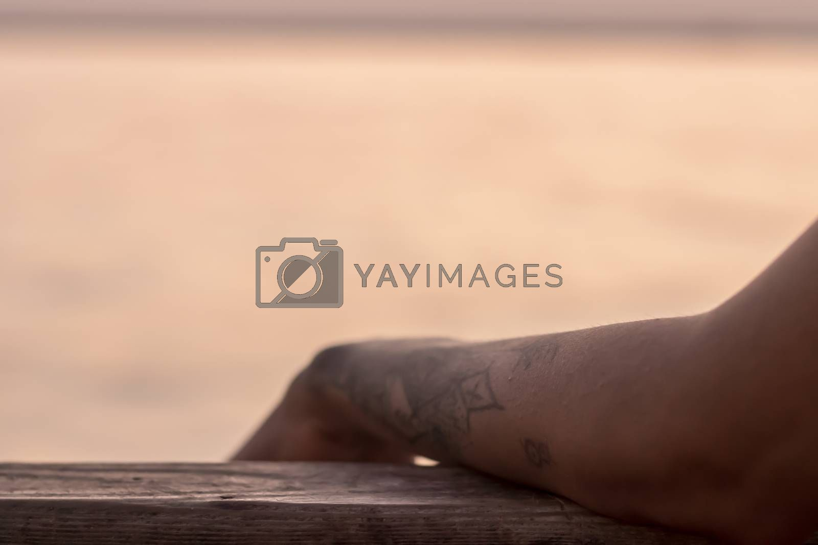 a good looking partial closeup shoot to tattooed girl arm - blurry sea as background. photo has taken at izmir/turkey.