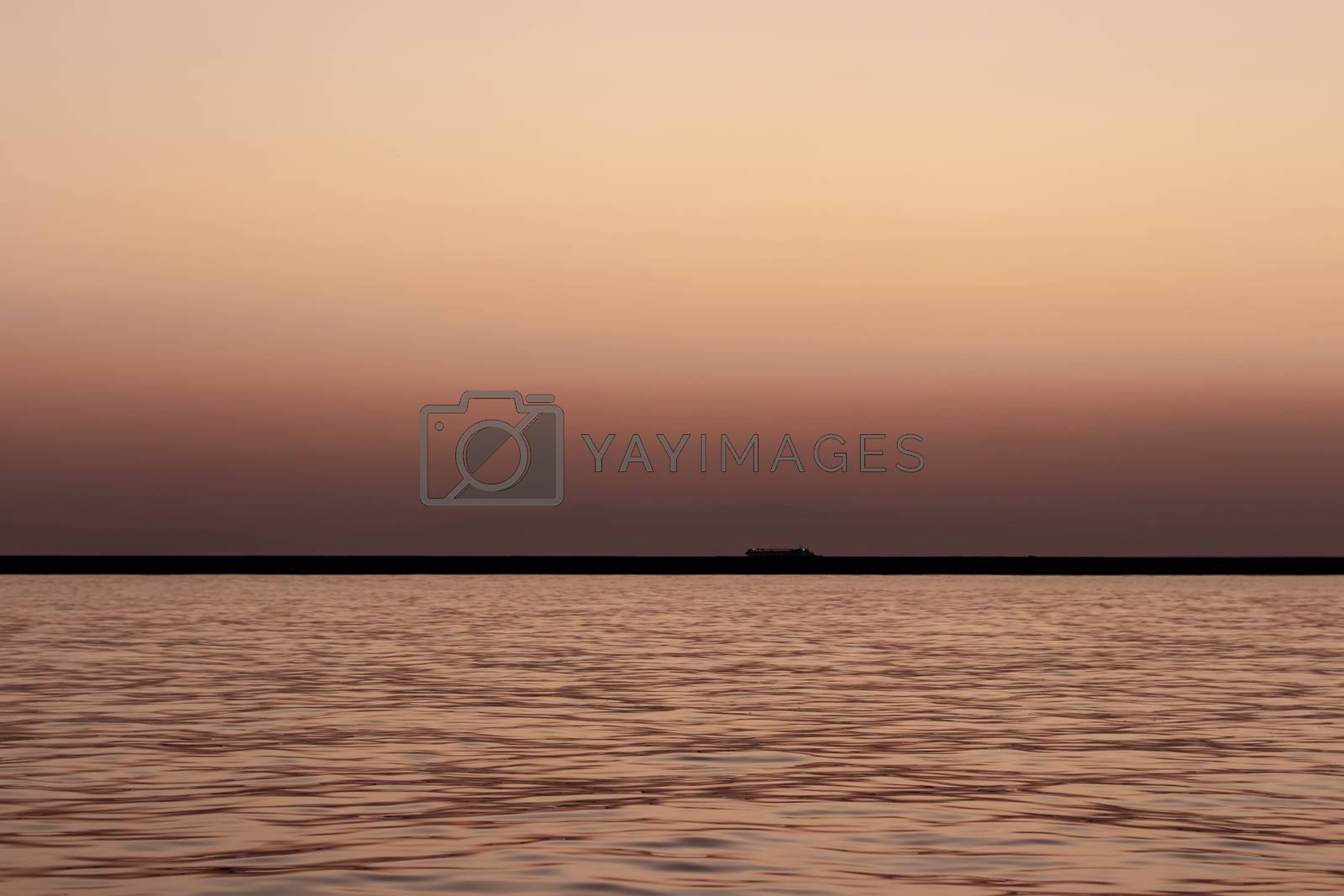 a wide seascape shoot with very well composed colors and black horizon from izmir bay - orange color dominated. photo has taken at izmir/turkey.