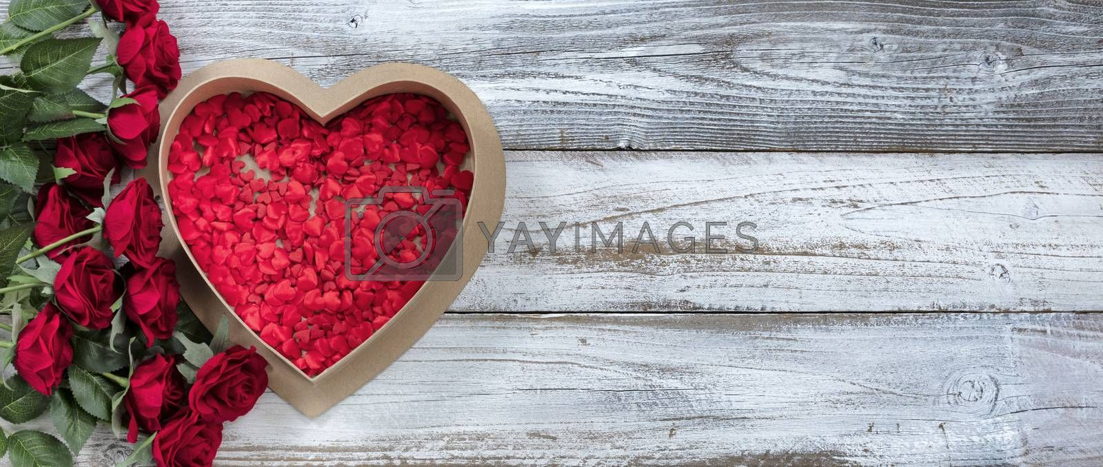 Happy Valentines Day gift box filled with tiny hearts and red roses on white rustic wood