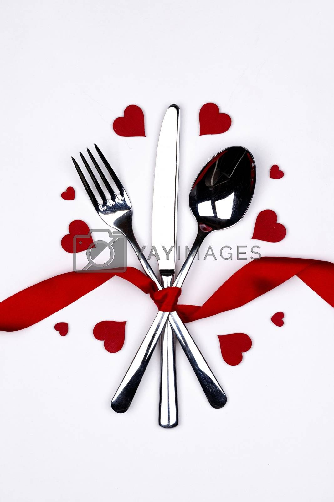 Cutlery set tied with silk ribbon and hearts on white background Valentine day dinner concept