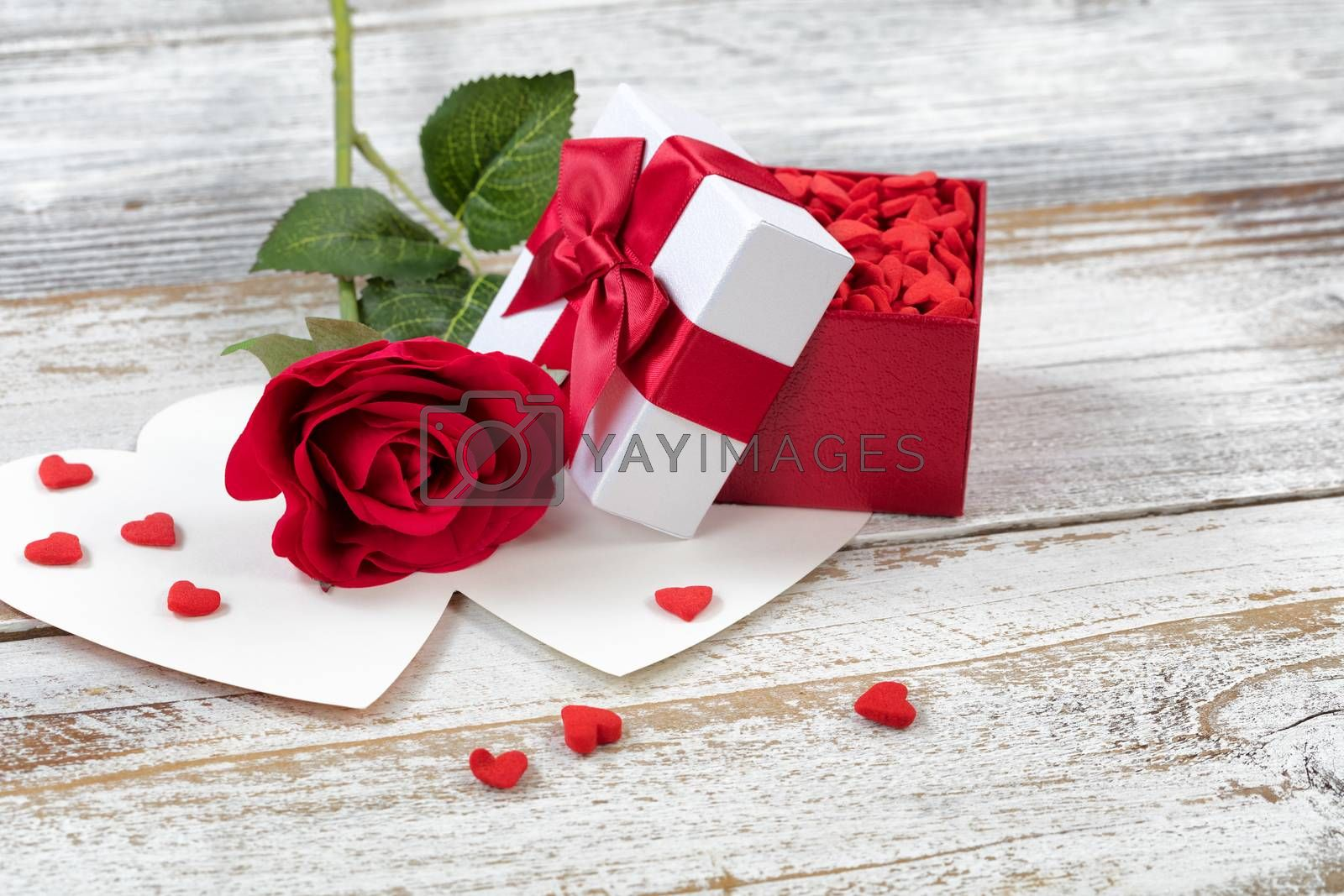 Open Valentines gift box filled with candies and single red rose on rustic white wood in close up view
