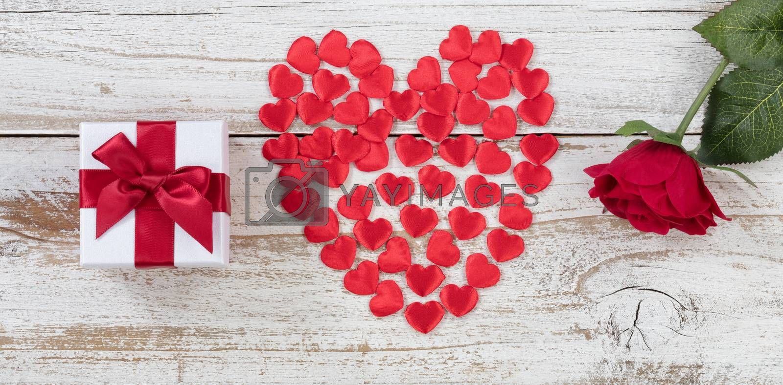 Filled red heart shapes, gift box and single rose on rustic white wood in flat lay view