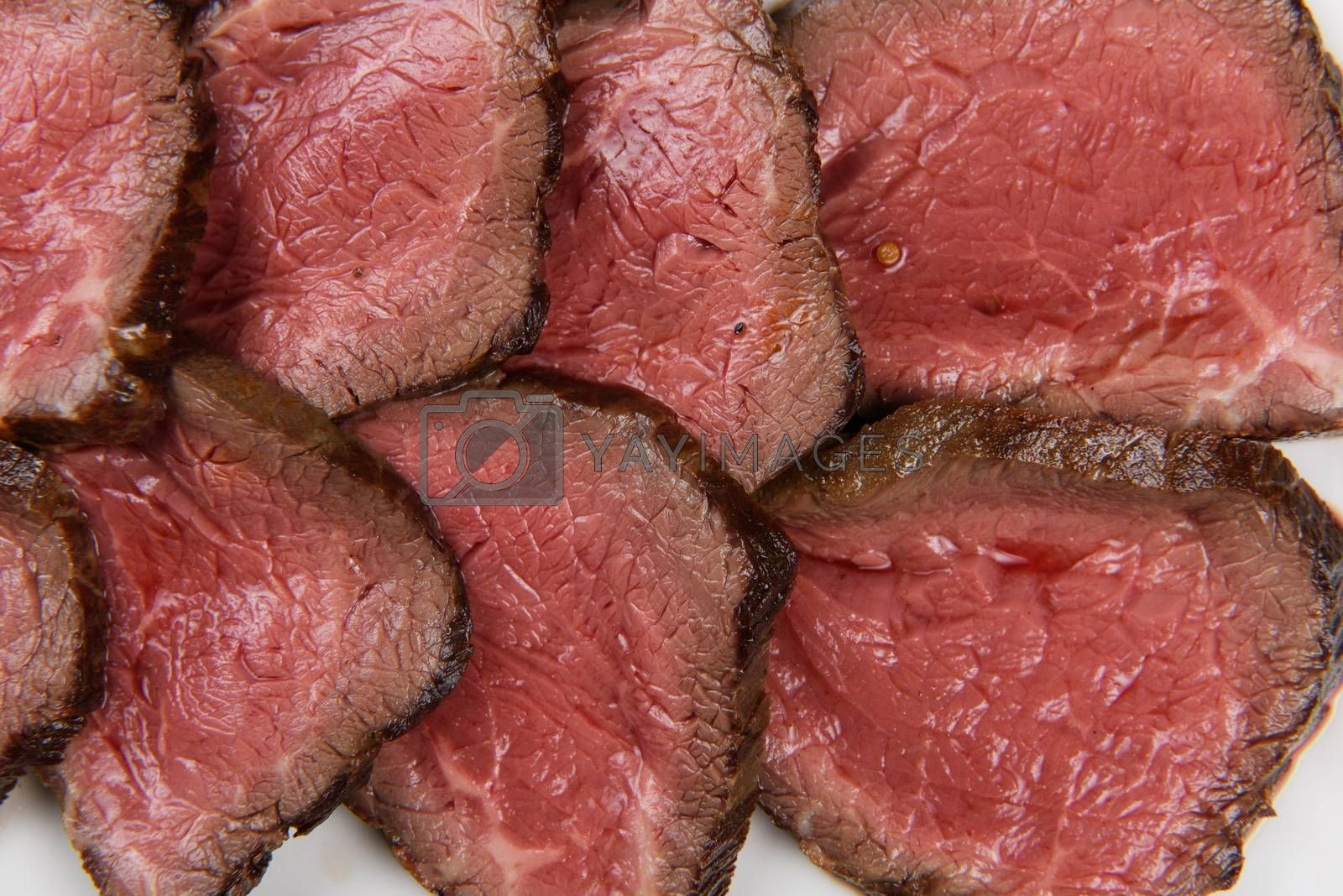 Plate with meat cutting and fresh greens on white plate