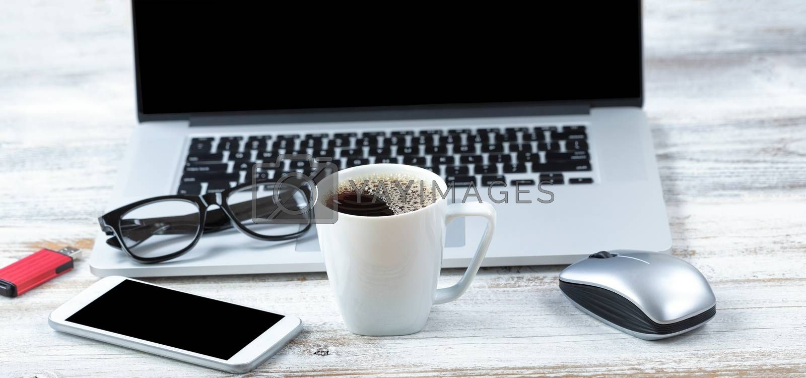 Cup of fresh coffee with workstation technology in background for business or education use