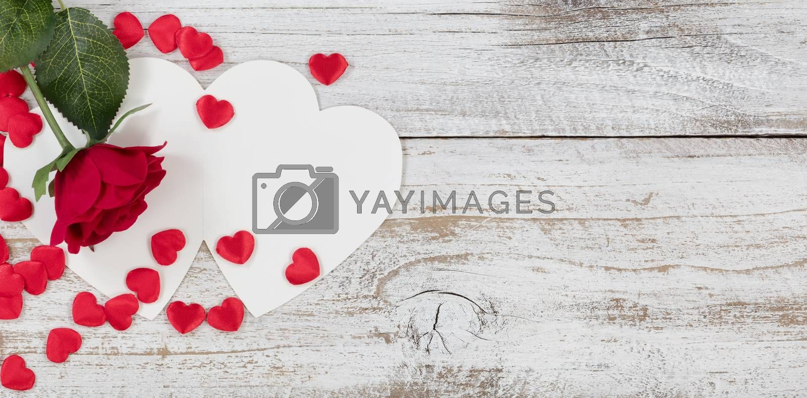 Valentines card with red heart shapes and a single rose on rustic white wood in flat lay view