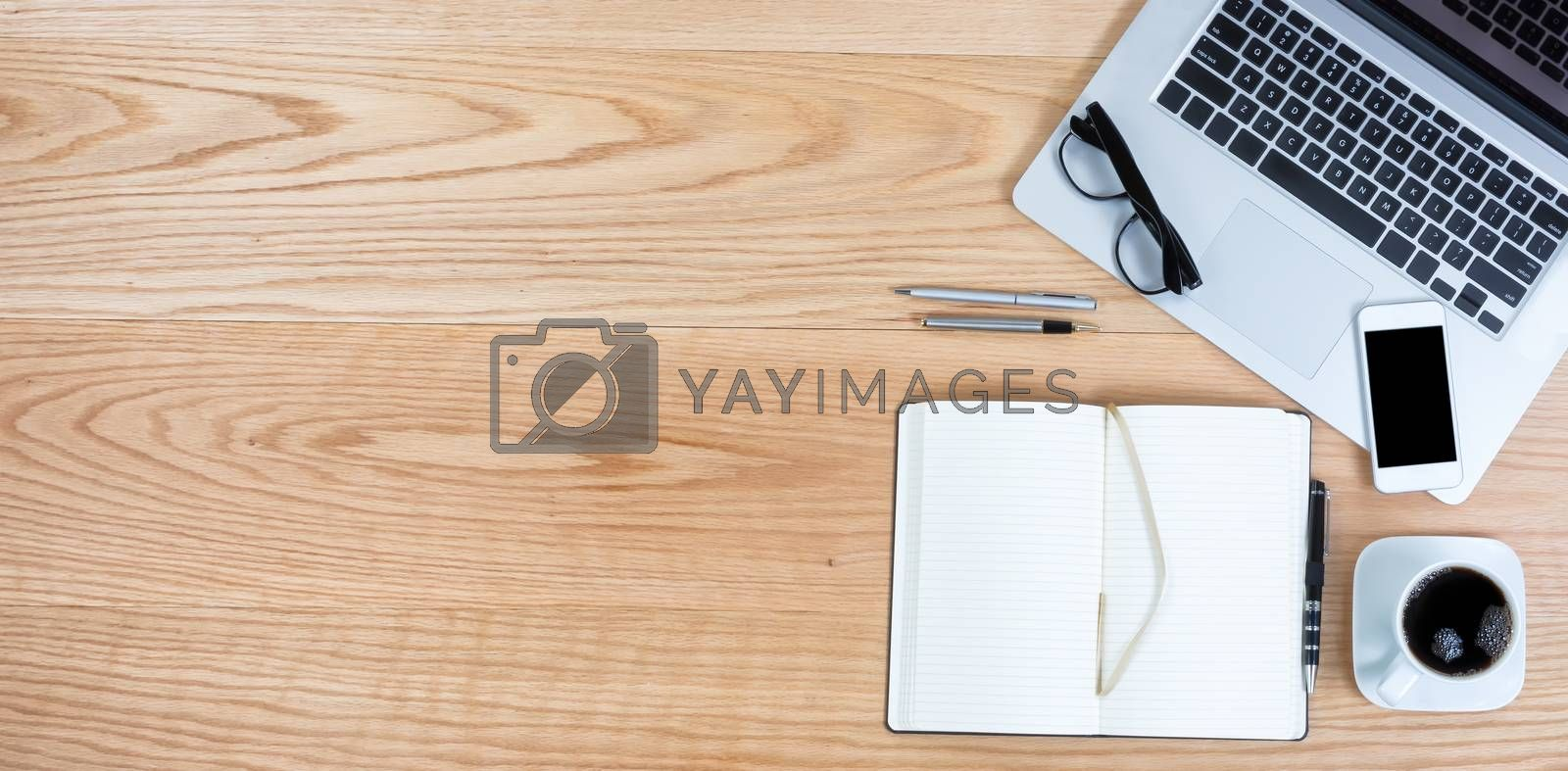 Clean red oak wooden desktop with laptop computer, smart phone, black coffee and writing materials