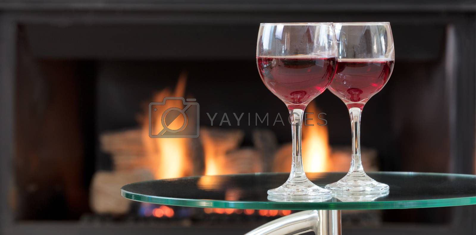 Two glasses of red wine on top of glass table with glowing fireplace in background