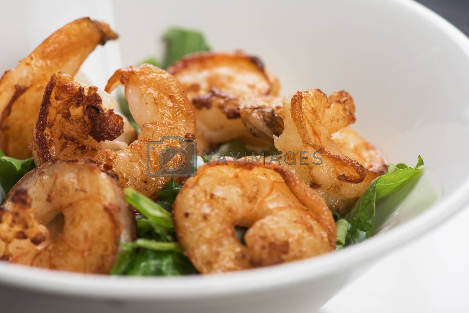 Fried shrimps with yogurt sauce and greens on plate