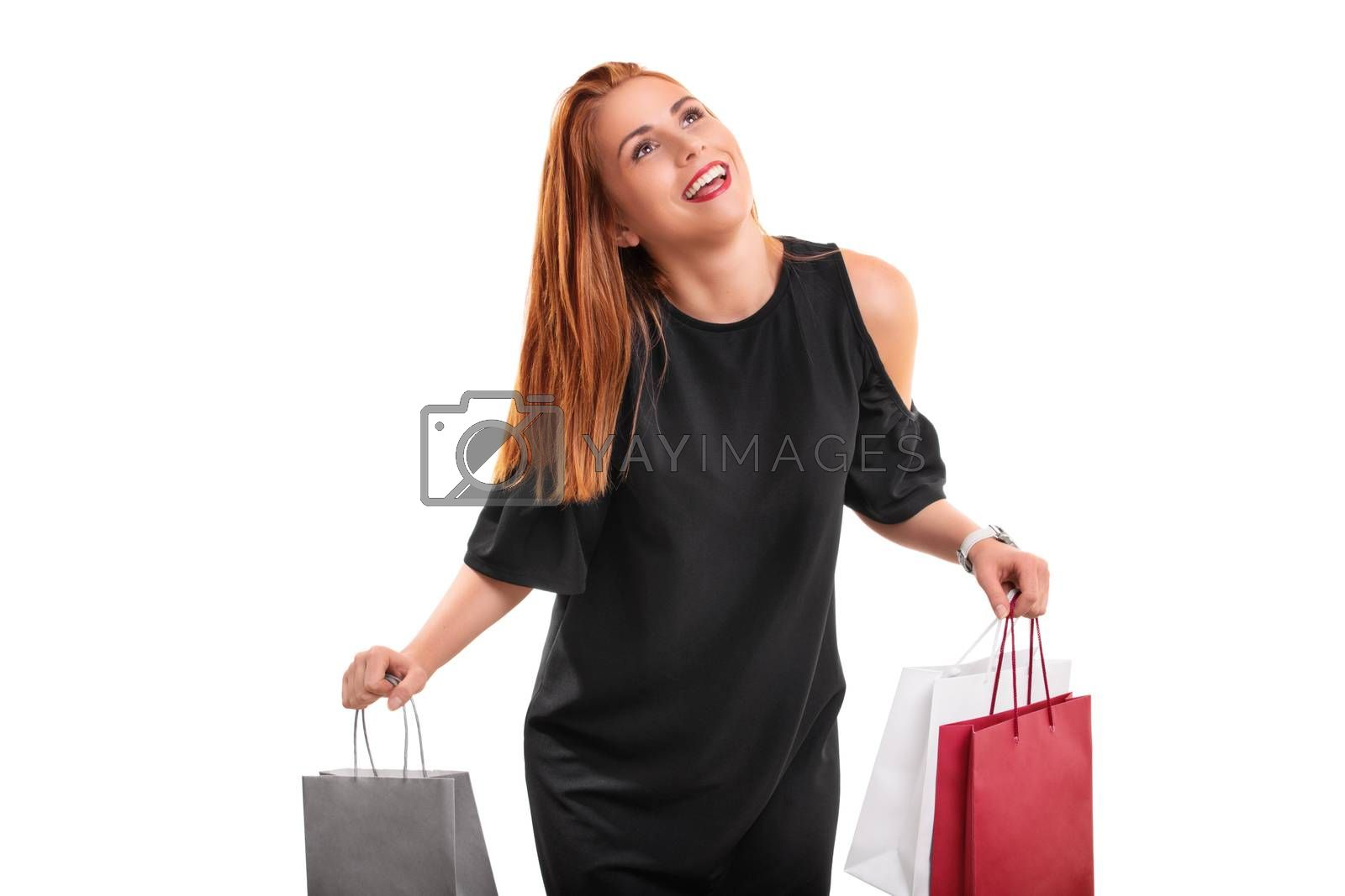 Sale, shopping concept. Excited beautiful young woman with shopping bags in both hands, isolated on white background.