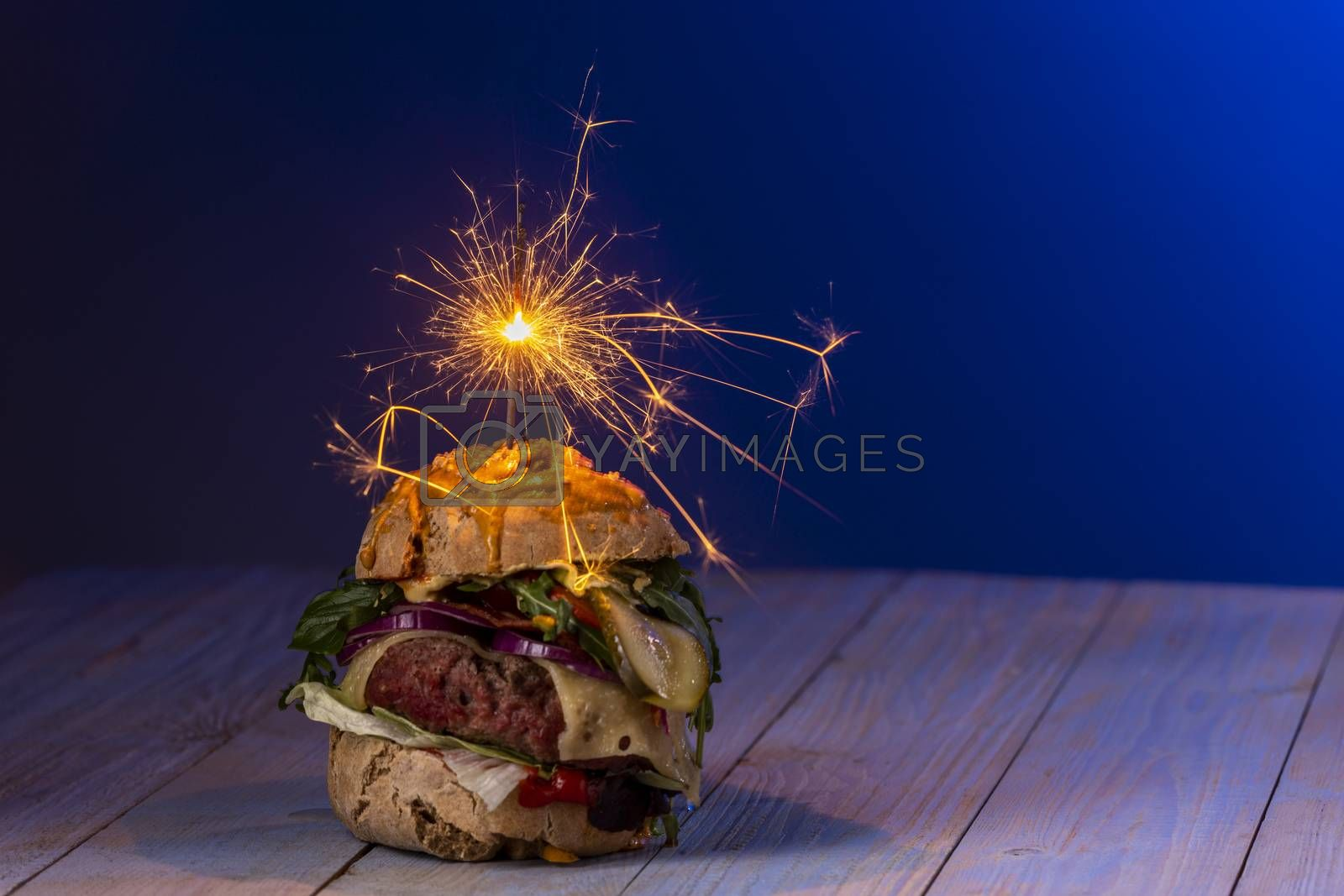 home made cheeseburger on dark wood  by bernjuer