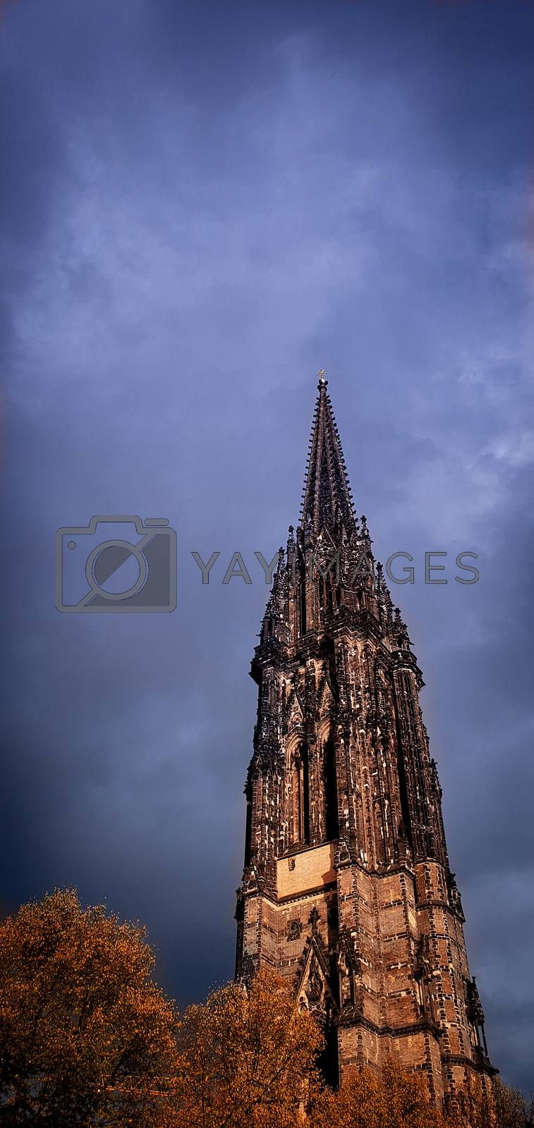 The burned spire of St. Nicholas church (St.-Nikolai-Kirche), a Gothic Revival cathedral who was one of the five Lutheran churches in Hamburg, Germany. Black church spire and stormy sky.