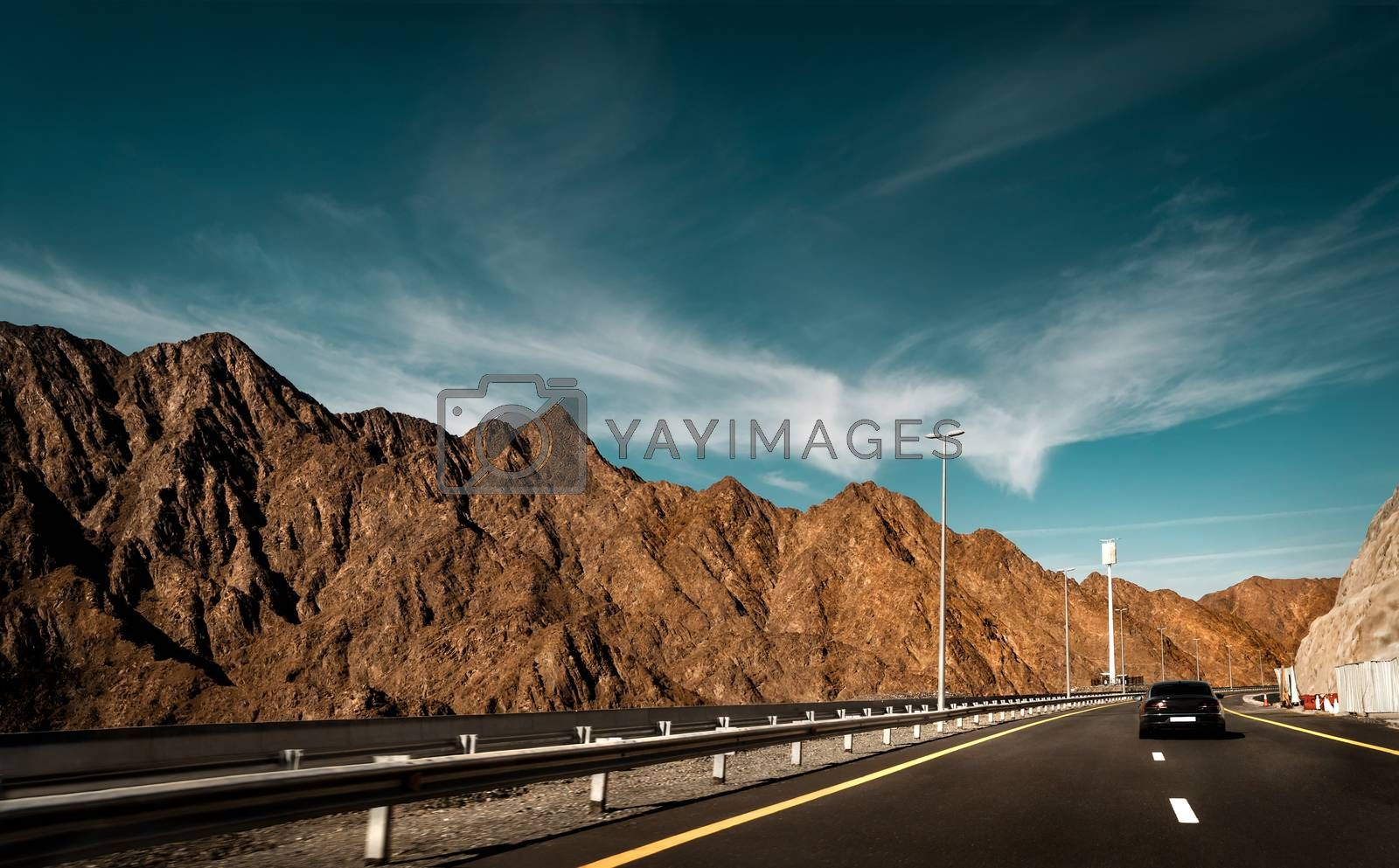 Road trip, car on the highway along beautiful mountains, vacation in Fujeira, UAE