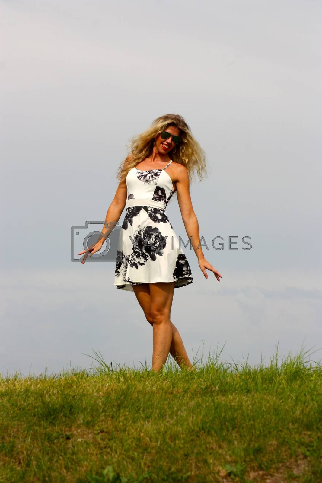 blonde in white with black flowers dress and sunglasses stands on green grass