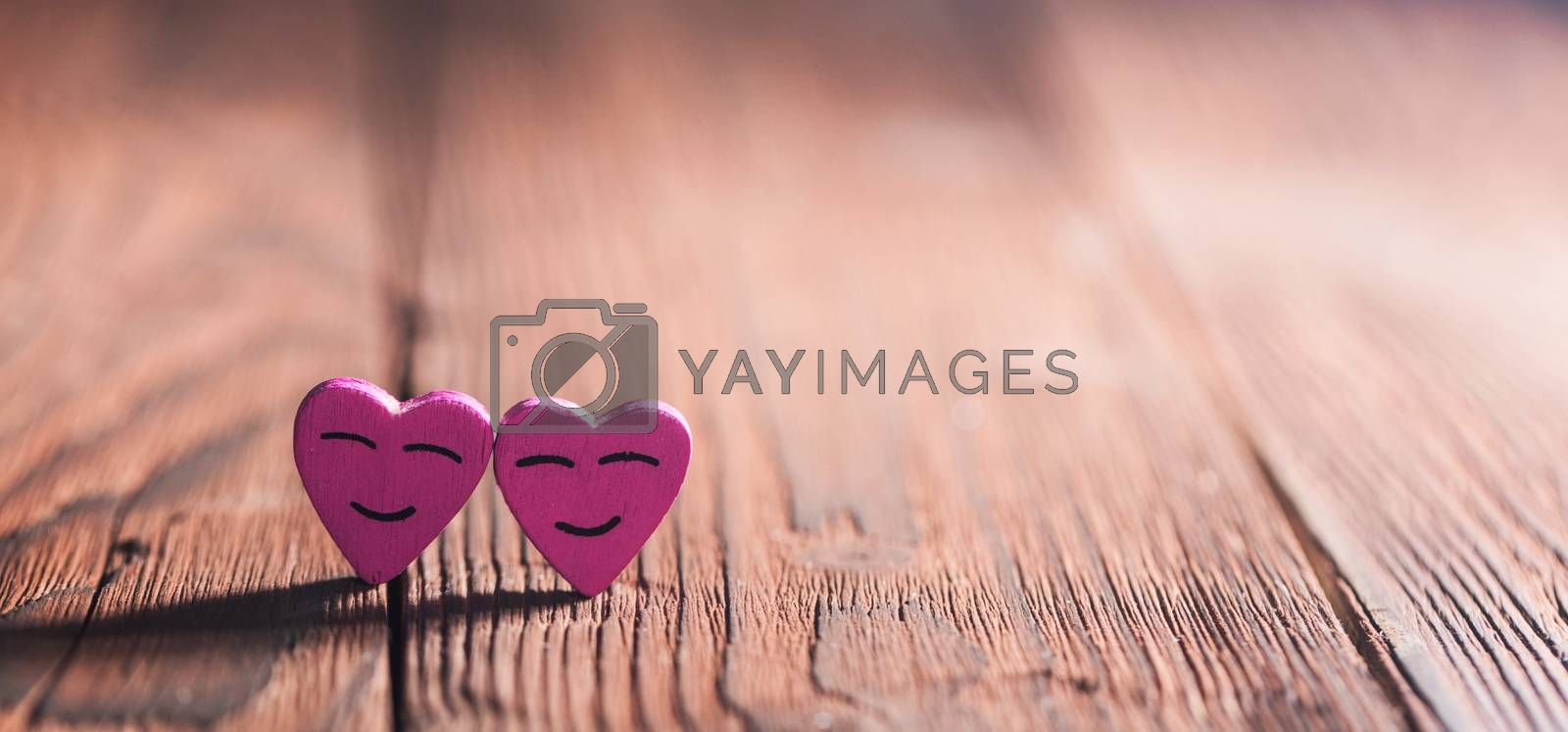 Two pink smiling hearts on wooden background with copy space for text