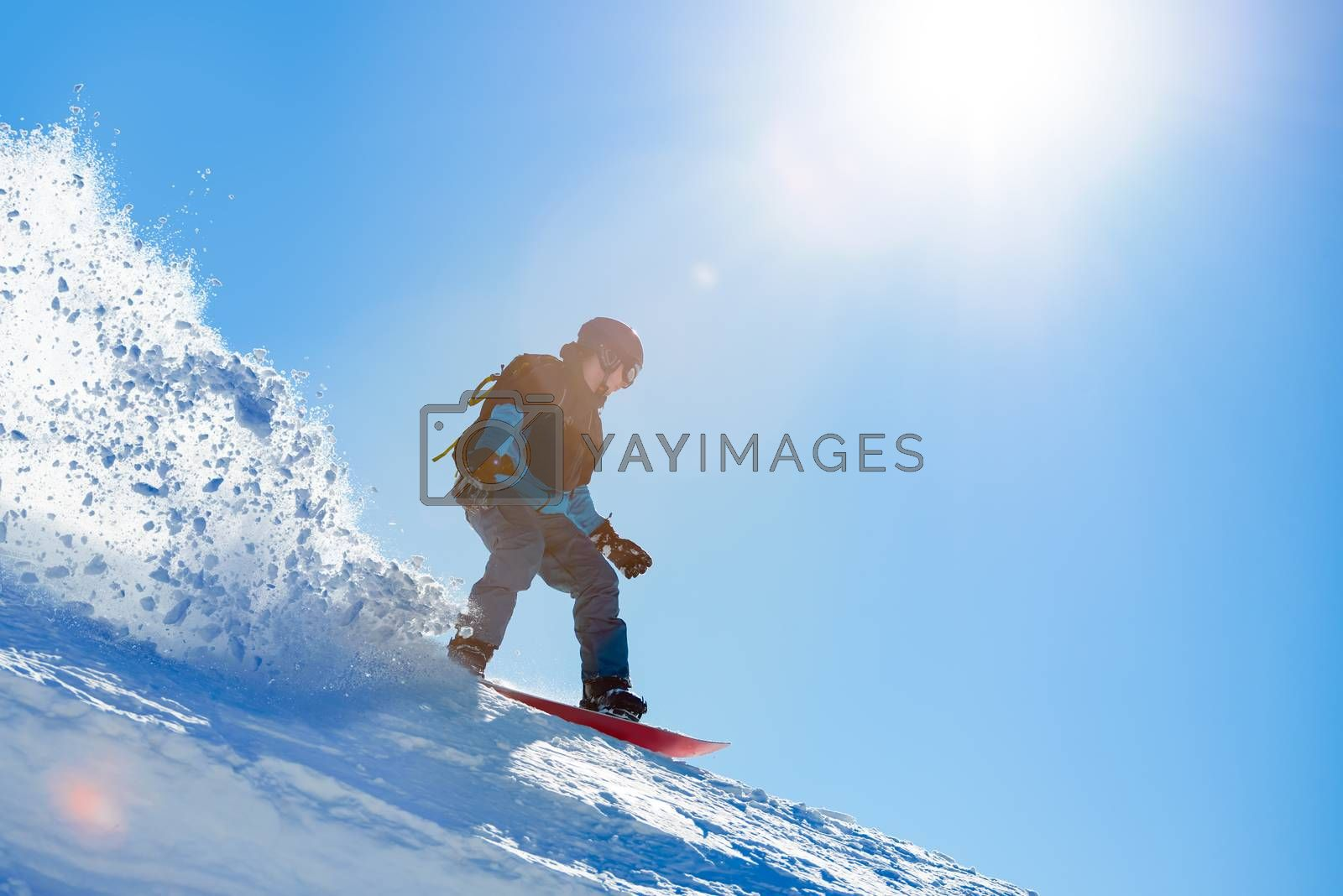 Snowboarder Riding Red Snowboard on the Slope in the Mountains in Bright Sun. Snowboarding and Extreme Winter Sports Concept.