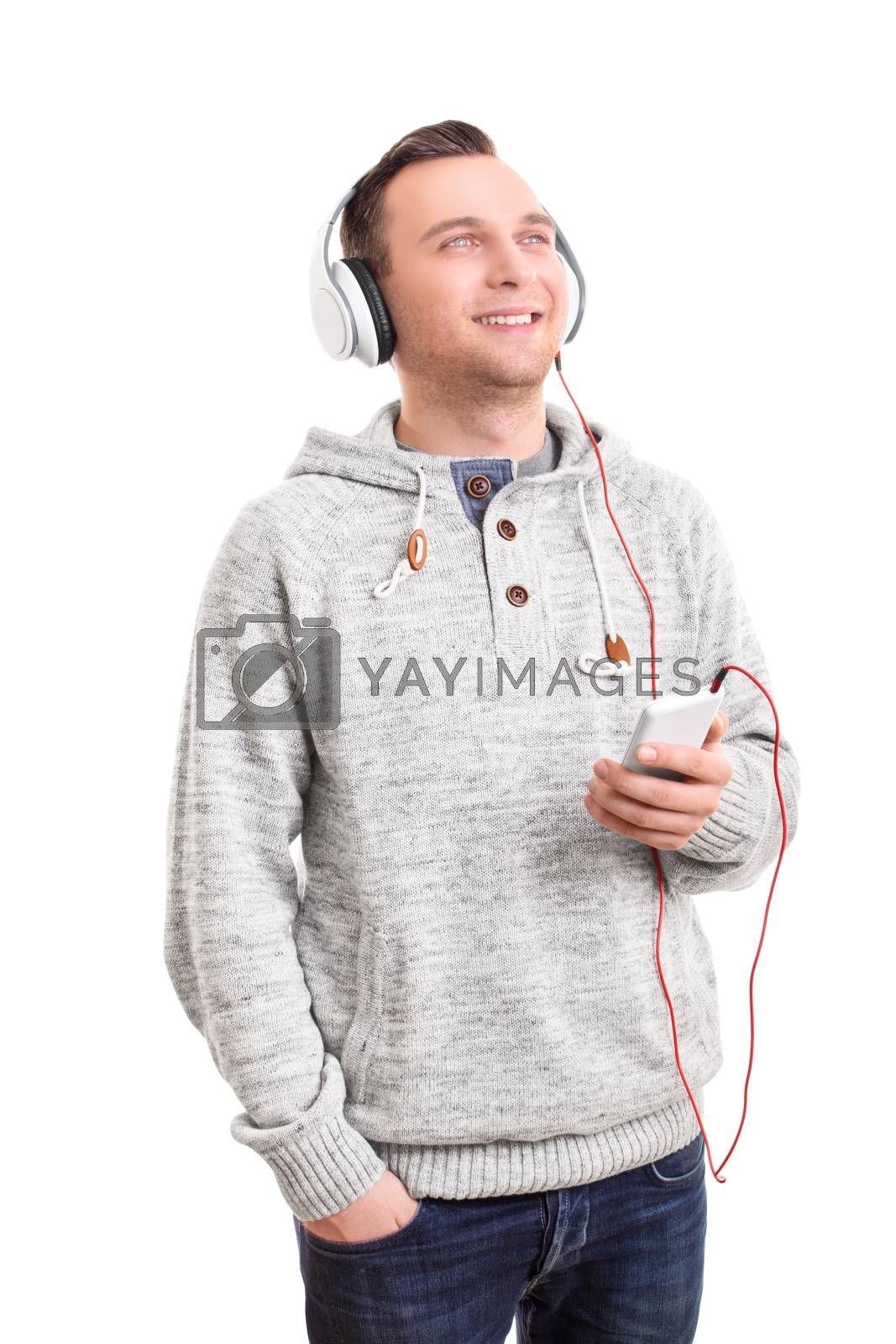 Music concept. Handsome casual young man with white headphones listening to music on his phone, enjoying and smiling, isolated on white background. Young man listening to music on his headphones.