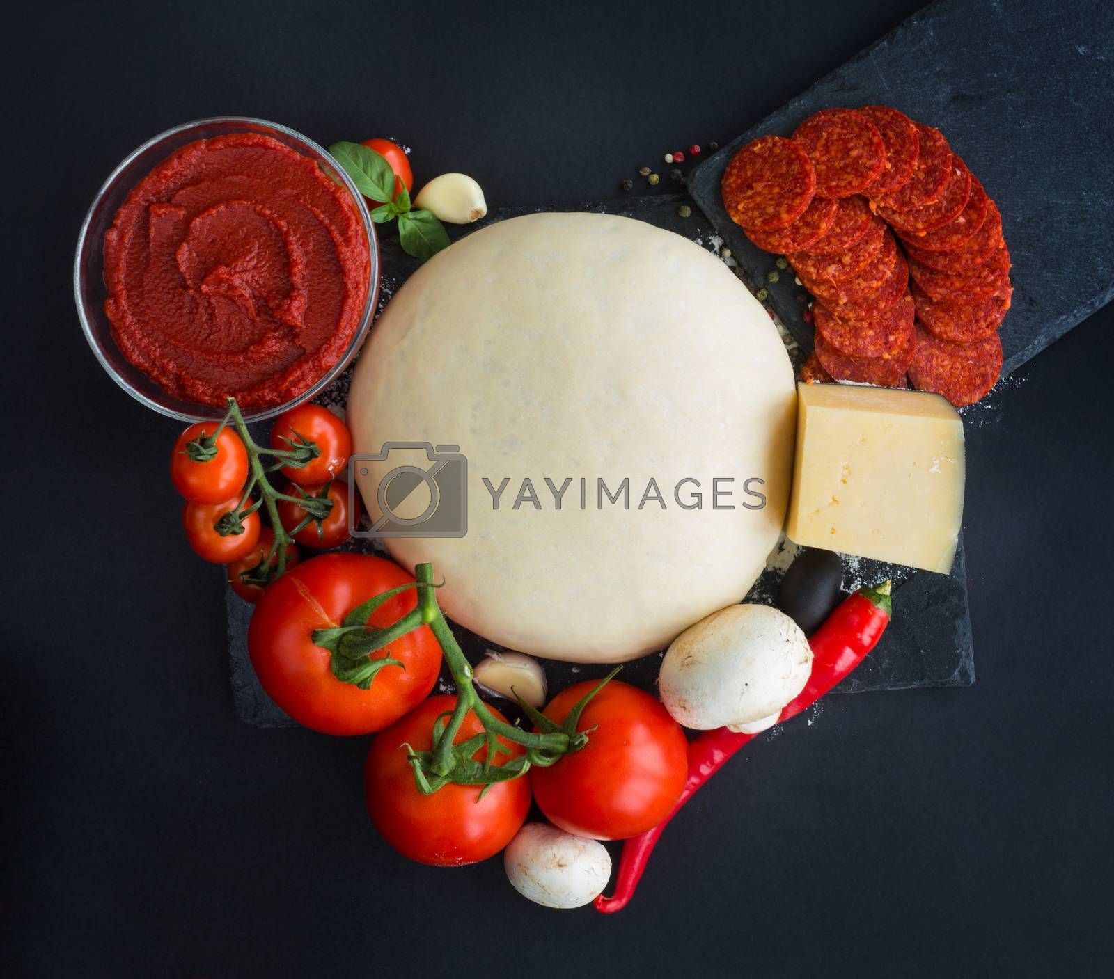 Raw dough for pizza and ingredients and spices on black table background in heart shape love food of Valentines day concept