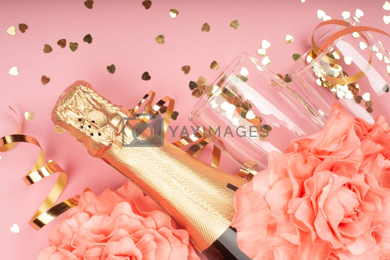 Valentines day champagne bottle flute glasses golden confetti hearts rose flowers and serpentine on pink background with copy space for text