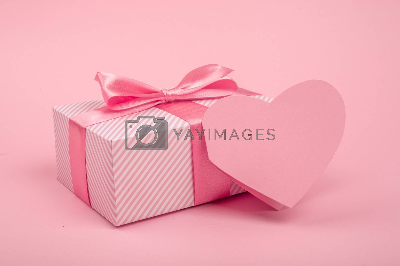 Valentine Day gift in a box wrapped in striped paper and tied with silk ribbon bow and heart shapes greeting card on pink background with copy space for text