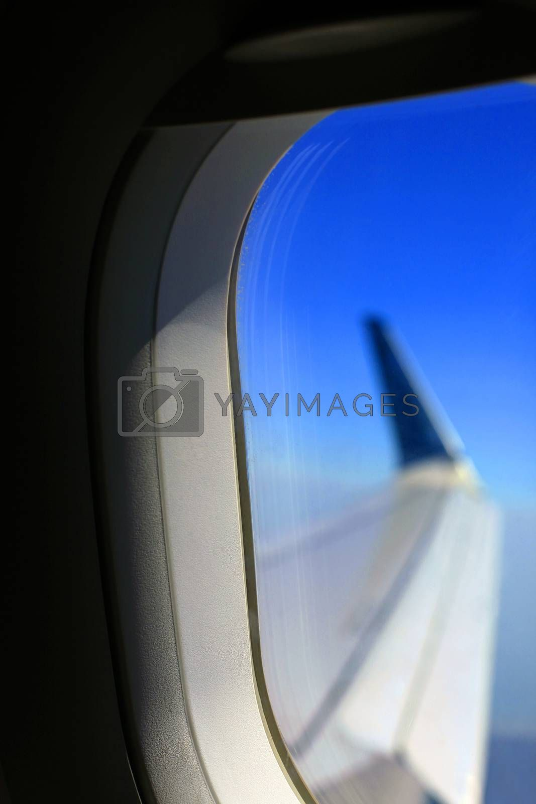 View from inside of plane through airplane window at wing