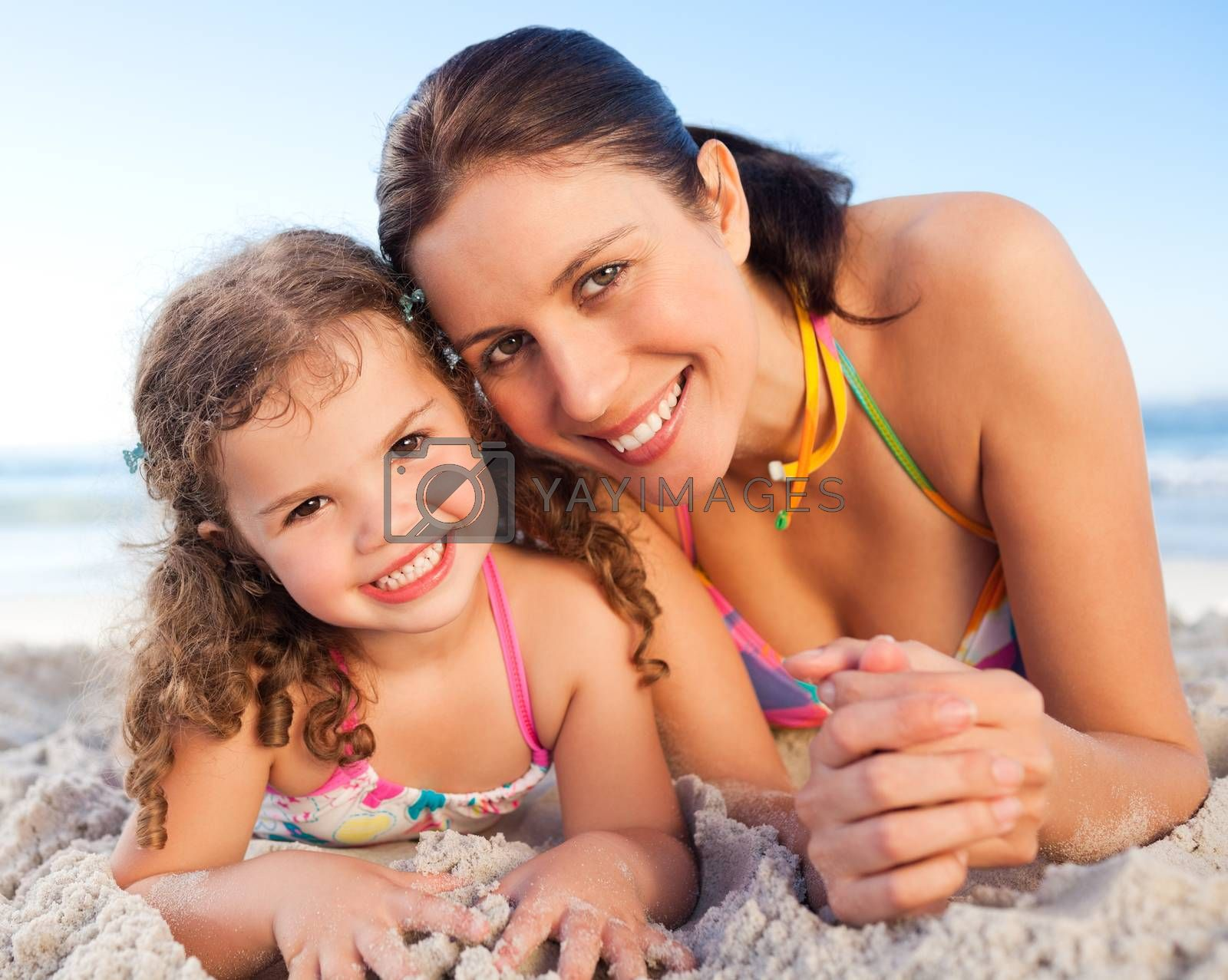 Mother and daughter lying down on the beach