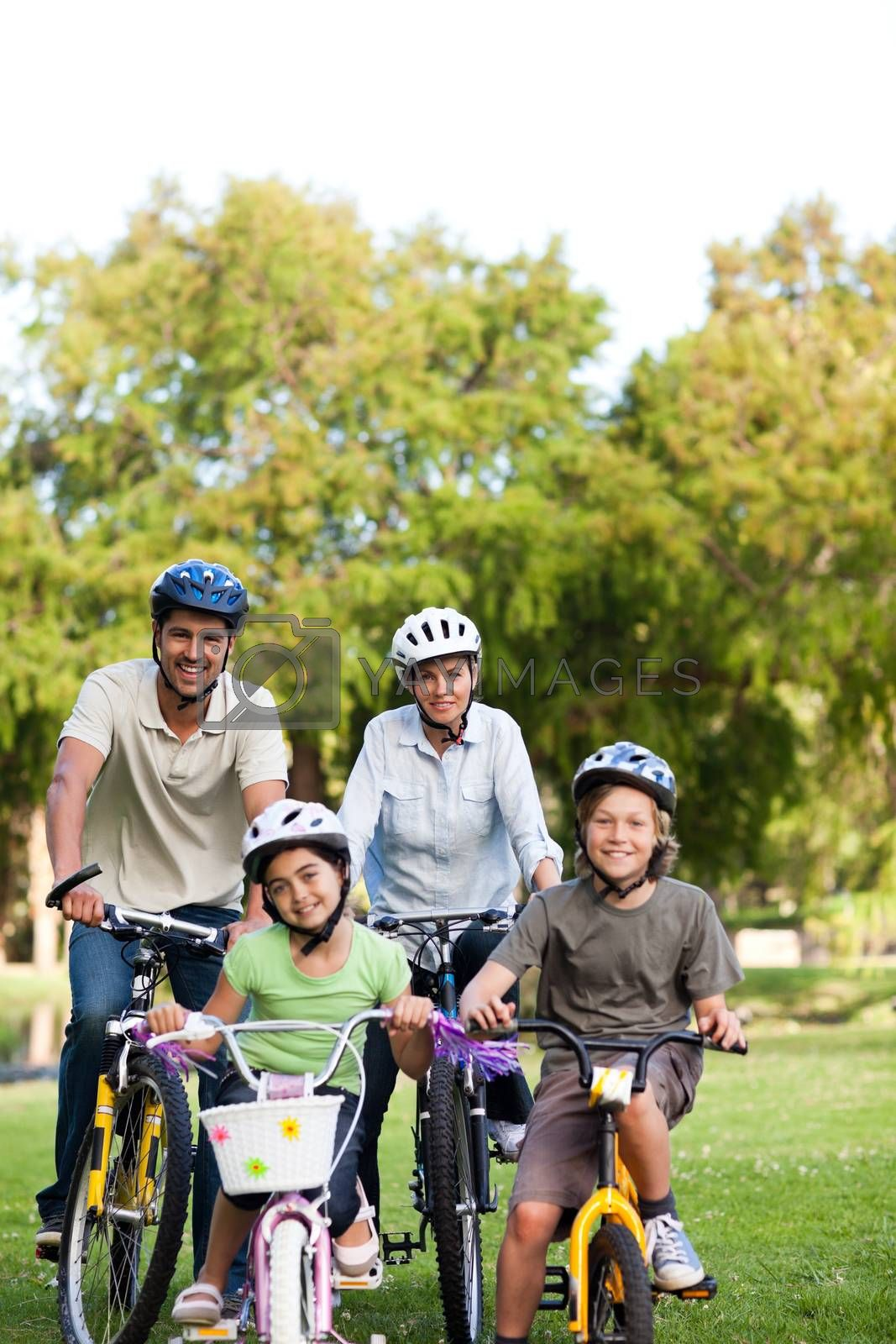 Family with their bikes during the summer in a park