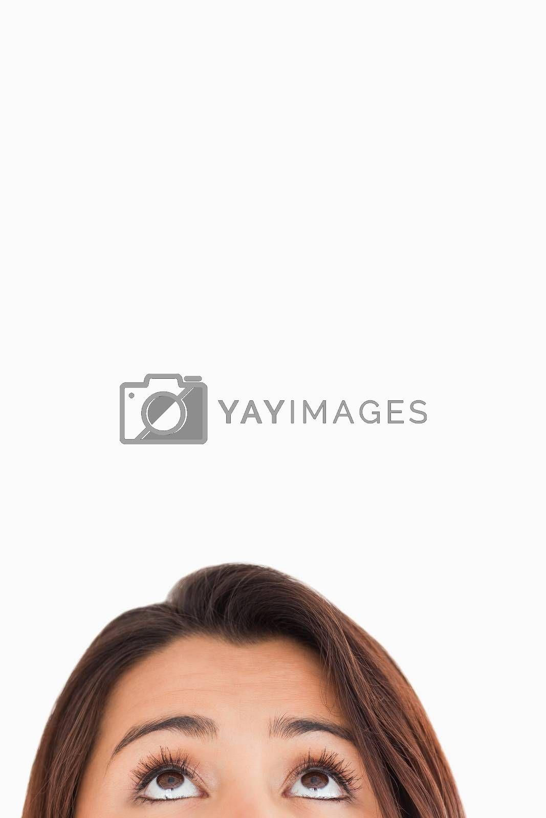 Woman eyes looking up while standing against a white background