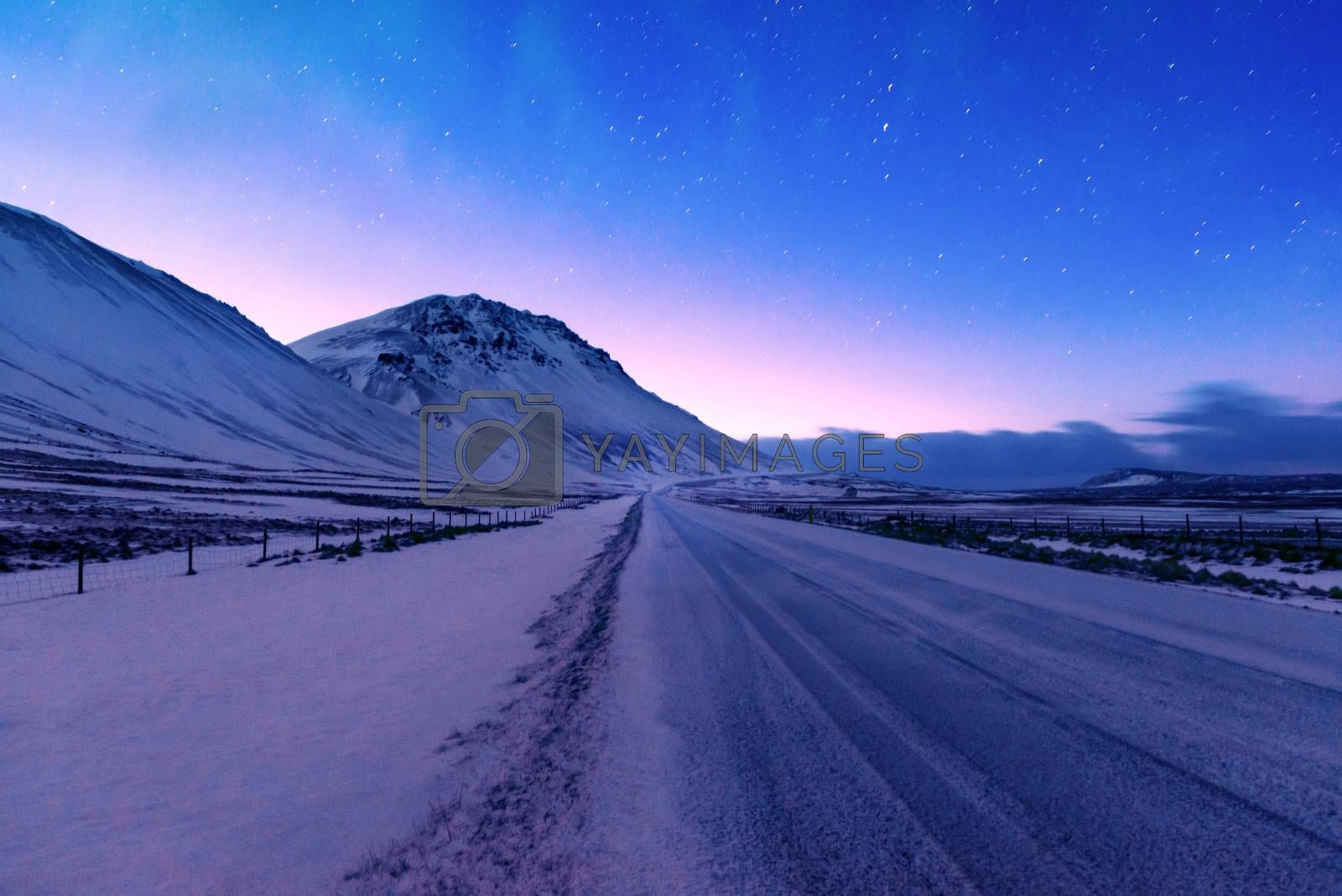 Iceland road trip, the highway along mountains covered with snow, amazing Icelandic landscape, picturesque wintertime view, the night shifts to a sunrise scene
