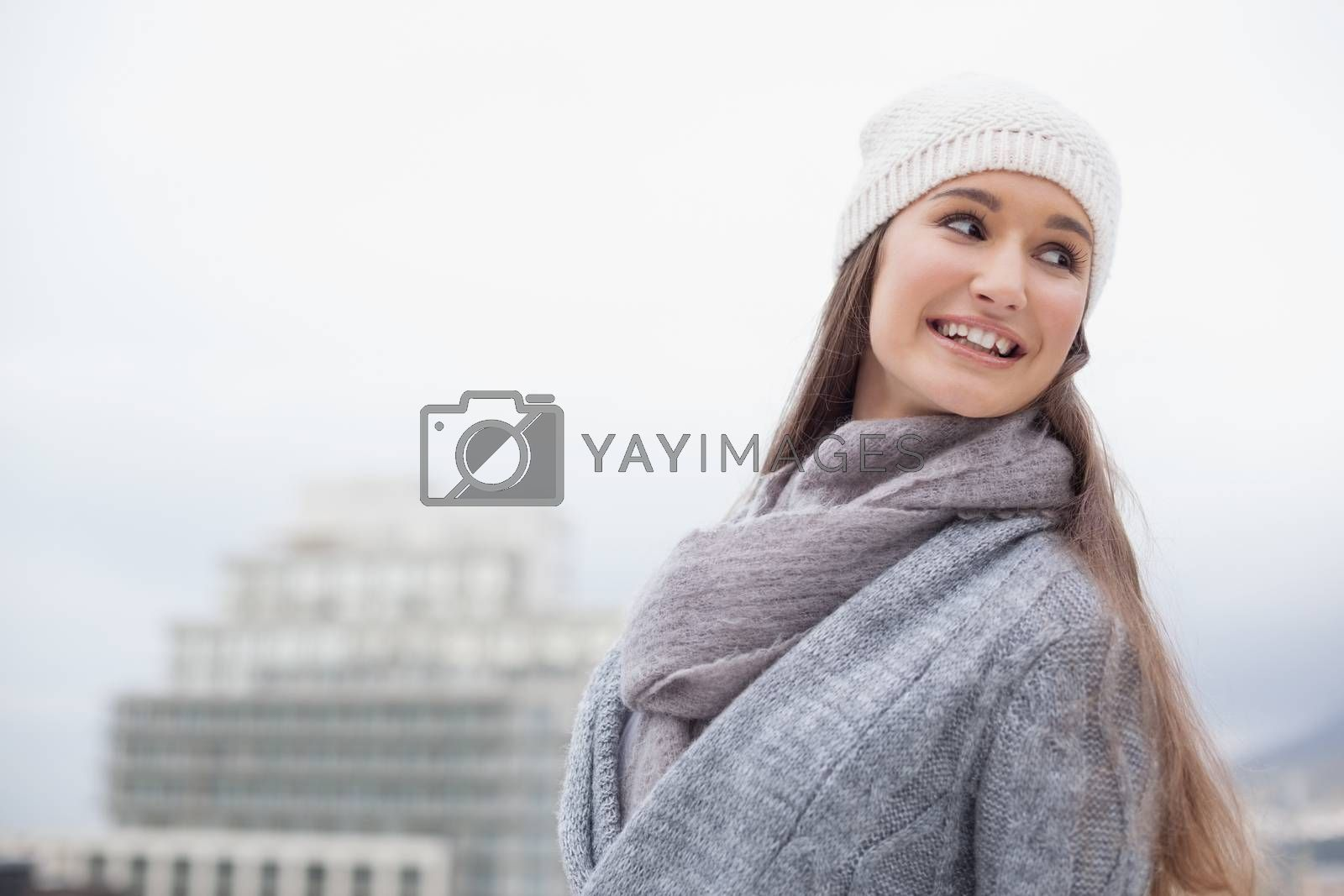 Pretty brunette with winter clothes on posing on a cold grey day