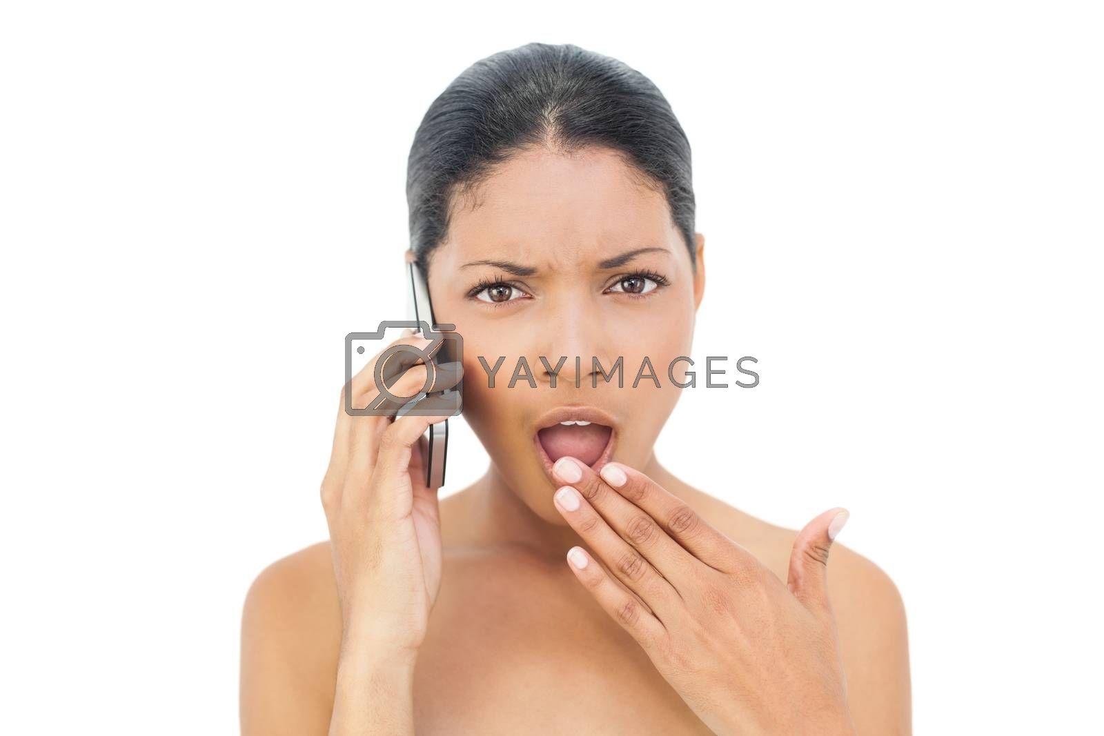 Shocked black haired model on the phone on white background