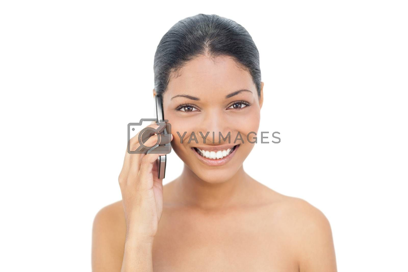 Smiling black haired model on the phone on white background