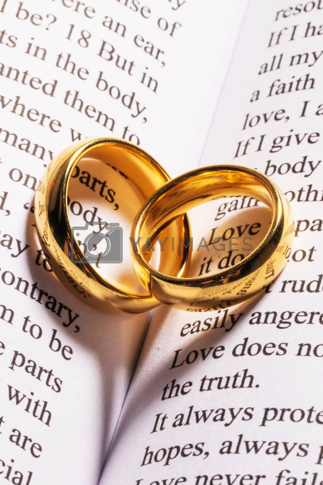 Two golden wedding rings on Holy bible book with heart shaped shadow close up