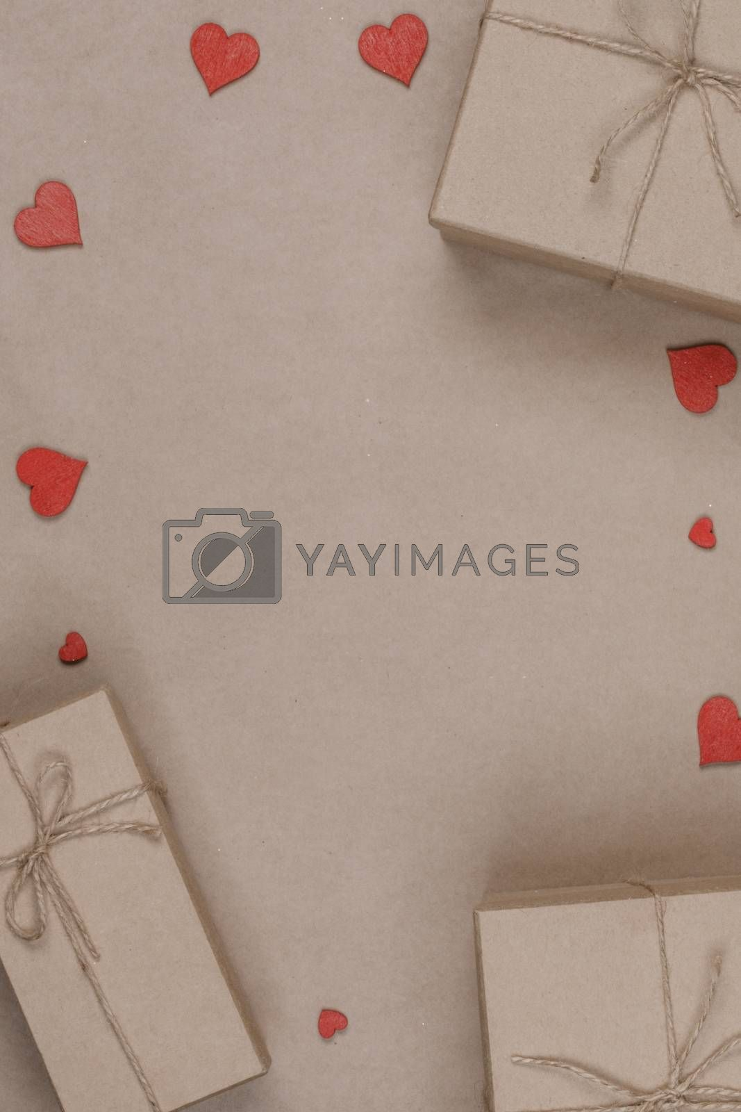 Boxes with gifts wrapped in brown craft paper and red paper hearts Valentines day concept
