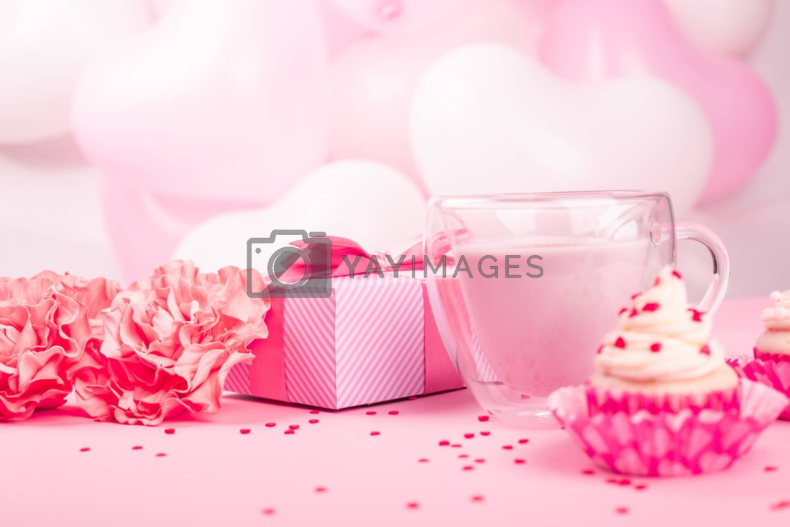 Valentine Day gift in a box wrapped in striped paper and tied with silk ribbon bow and dessert on pink balloons background with copy space for text