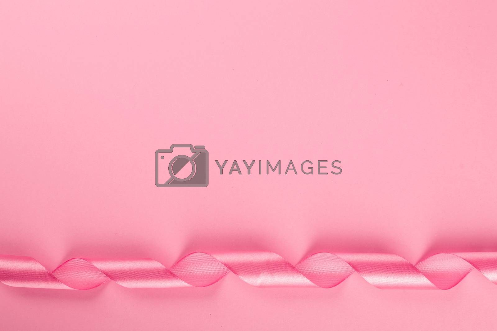 Valentine day background with pink curly satin ribbon on pink paper with copy space for text