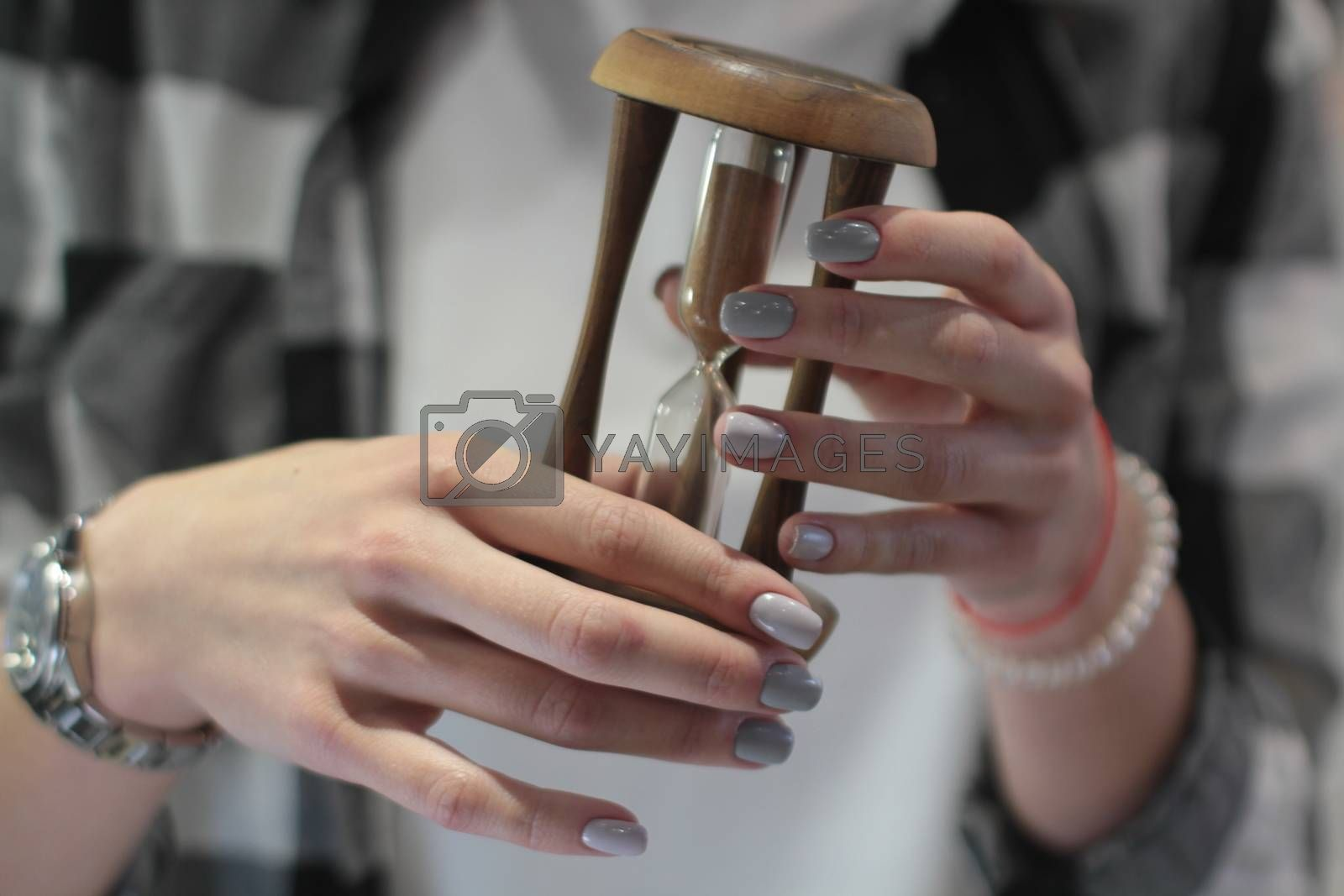 Beautiful female hands with manicure hold an hourglass. Beauty and fashion concept