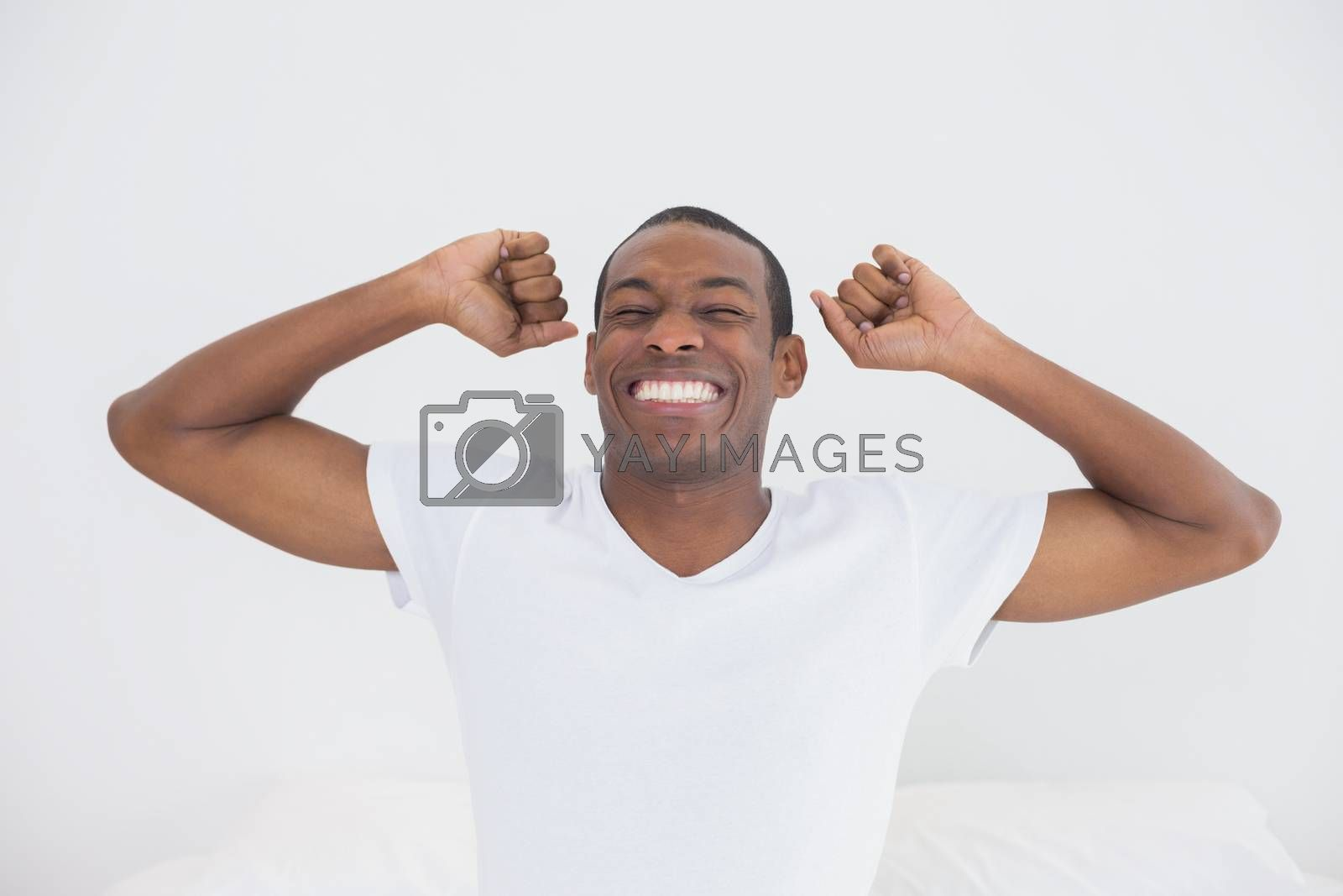 Smiling young Afro man waking up in bed and stretching his arms
