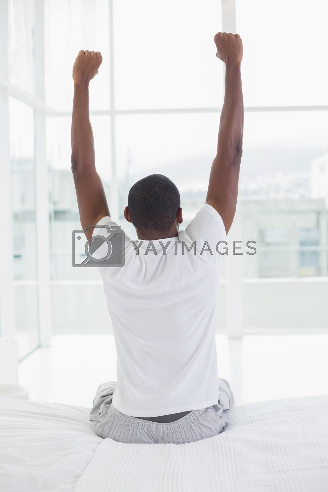 Rear view of a young Afro man waking up in bed and stretching his arms