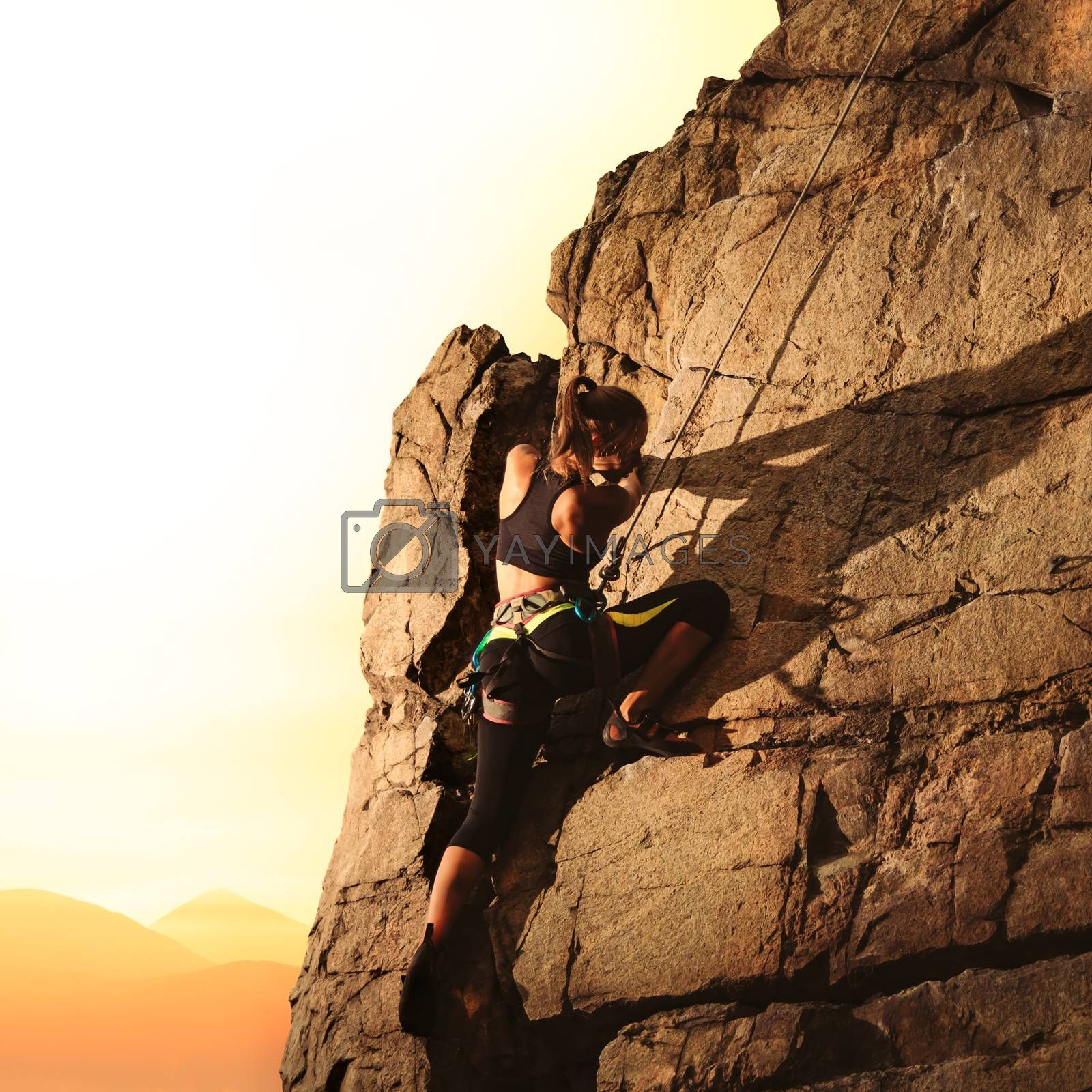 Woman Climber Climbing to the Top of the High Rock at Foggy Sunset in the Mountains. Adventure and Extreme Sport Concept