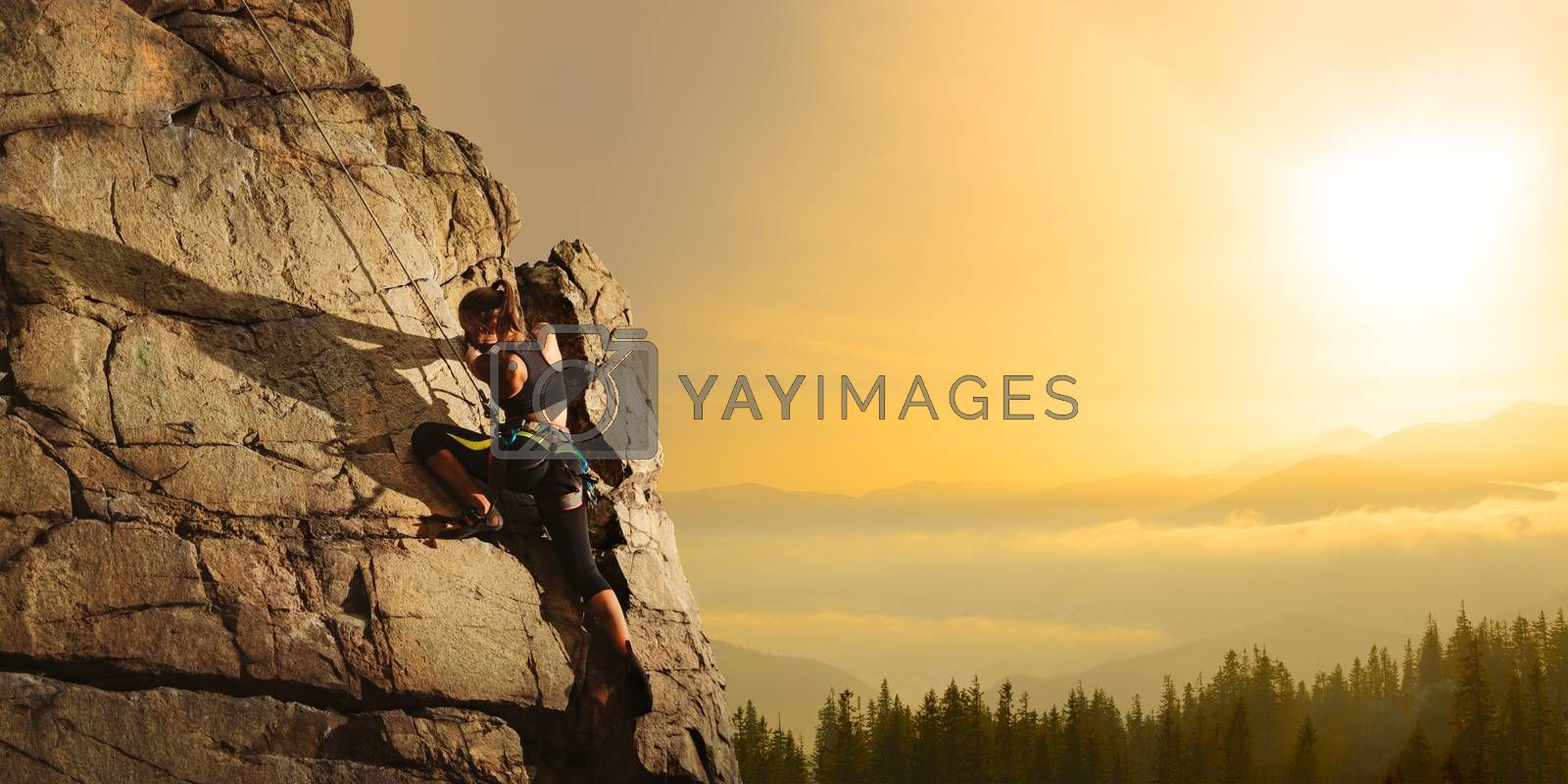 Climbing to the Top. Woman Climber on the High Rock at Foggy Sunset in the Mountains. Adventure and Extreme Sport Concept