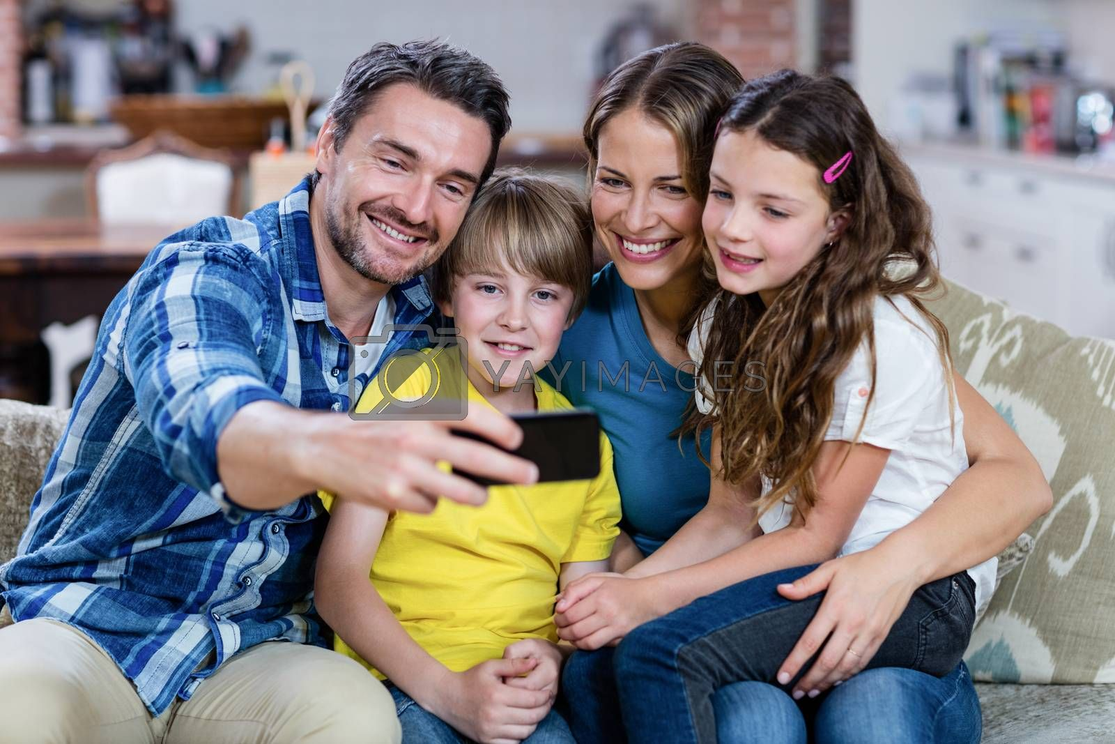 Happy family taking a selfie on mobile phone at home