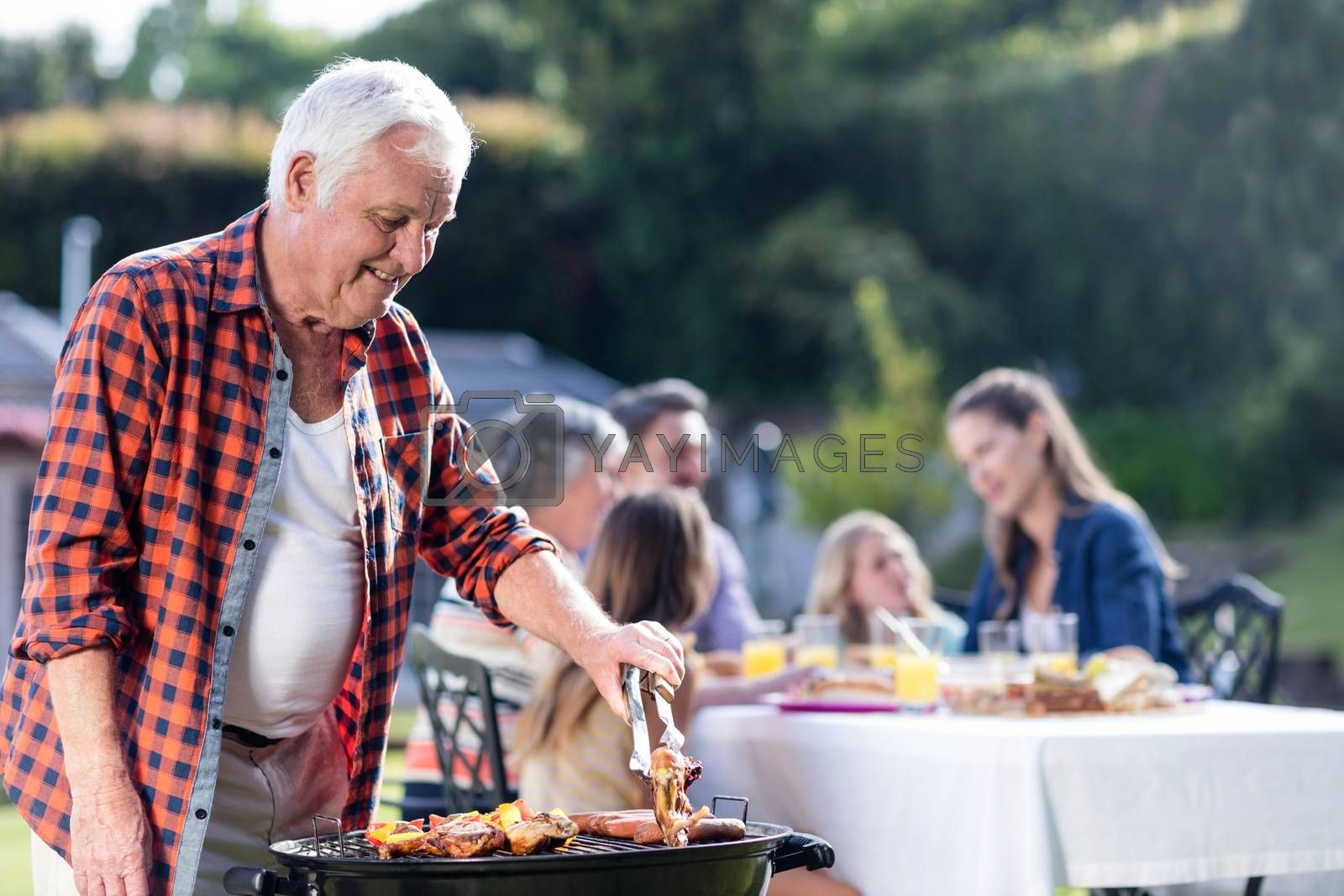 Senior man at barbecue grill while family having lunch in the garden