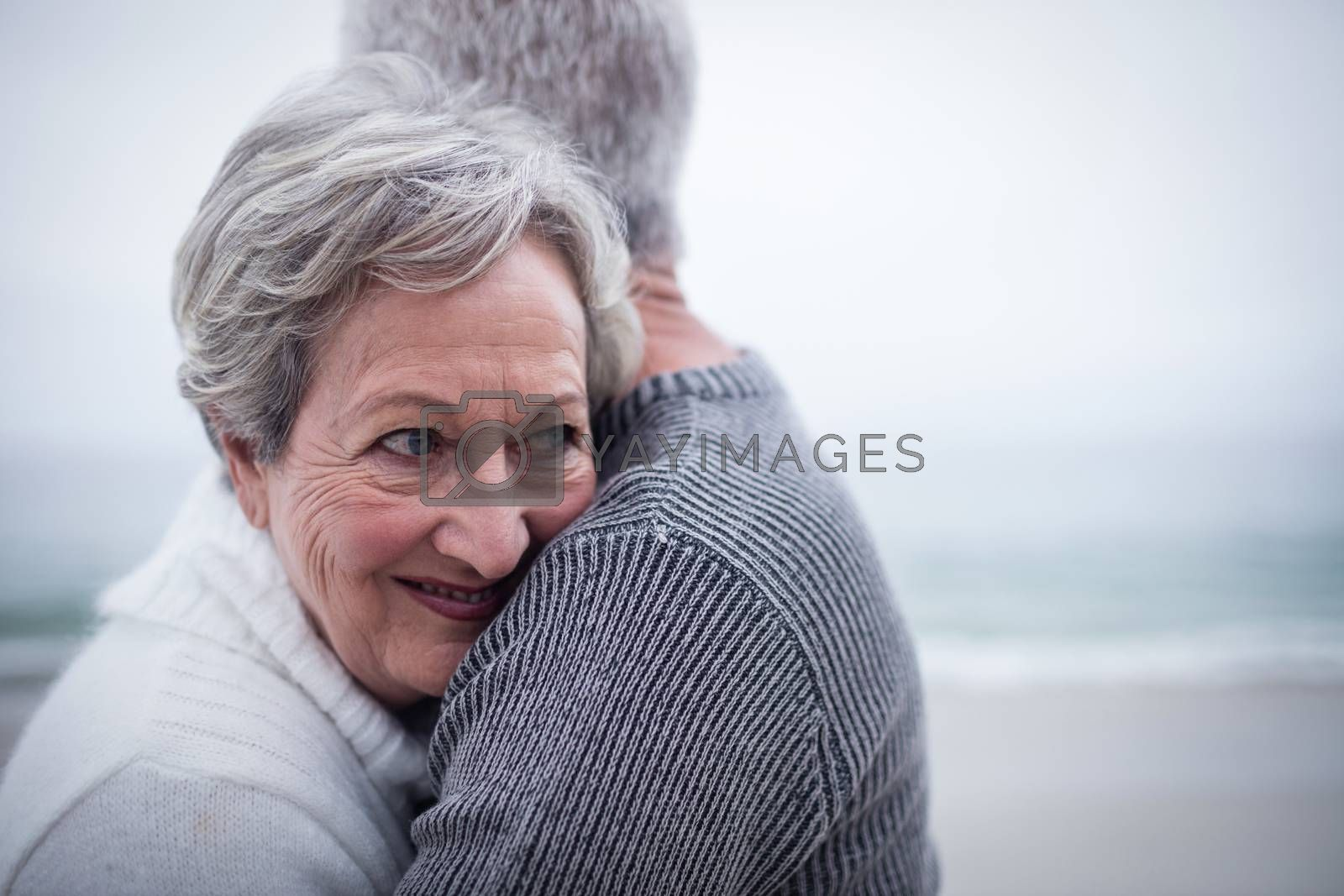 Happy senior couple embracing each other on the beach