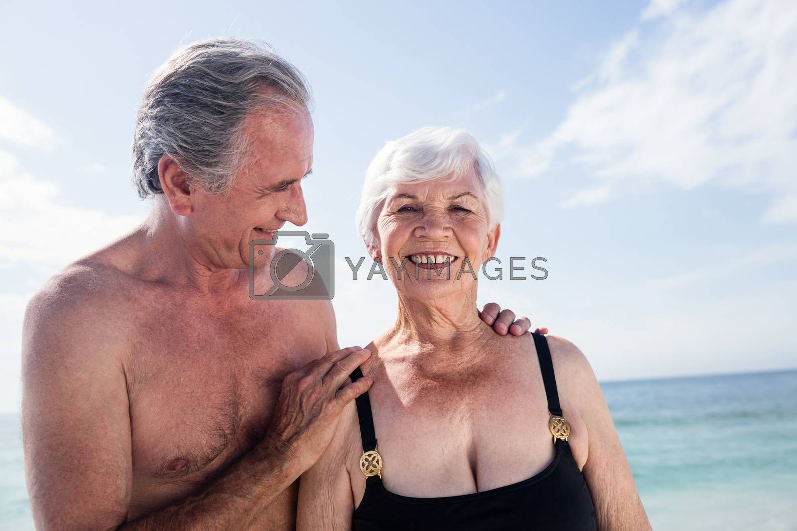 Senior couple embracing on beach at a sunny day