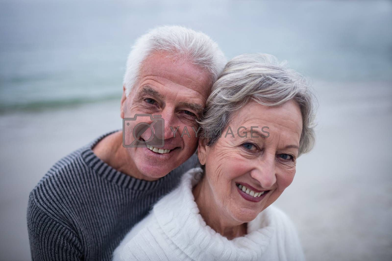 Portrait of senior couple embracing each other on the beach