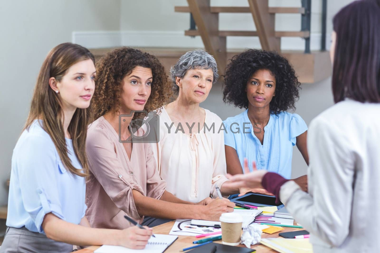 Woman giving presentation to her colleagues in office