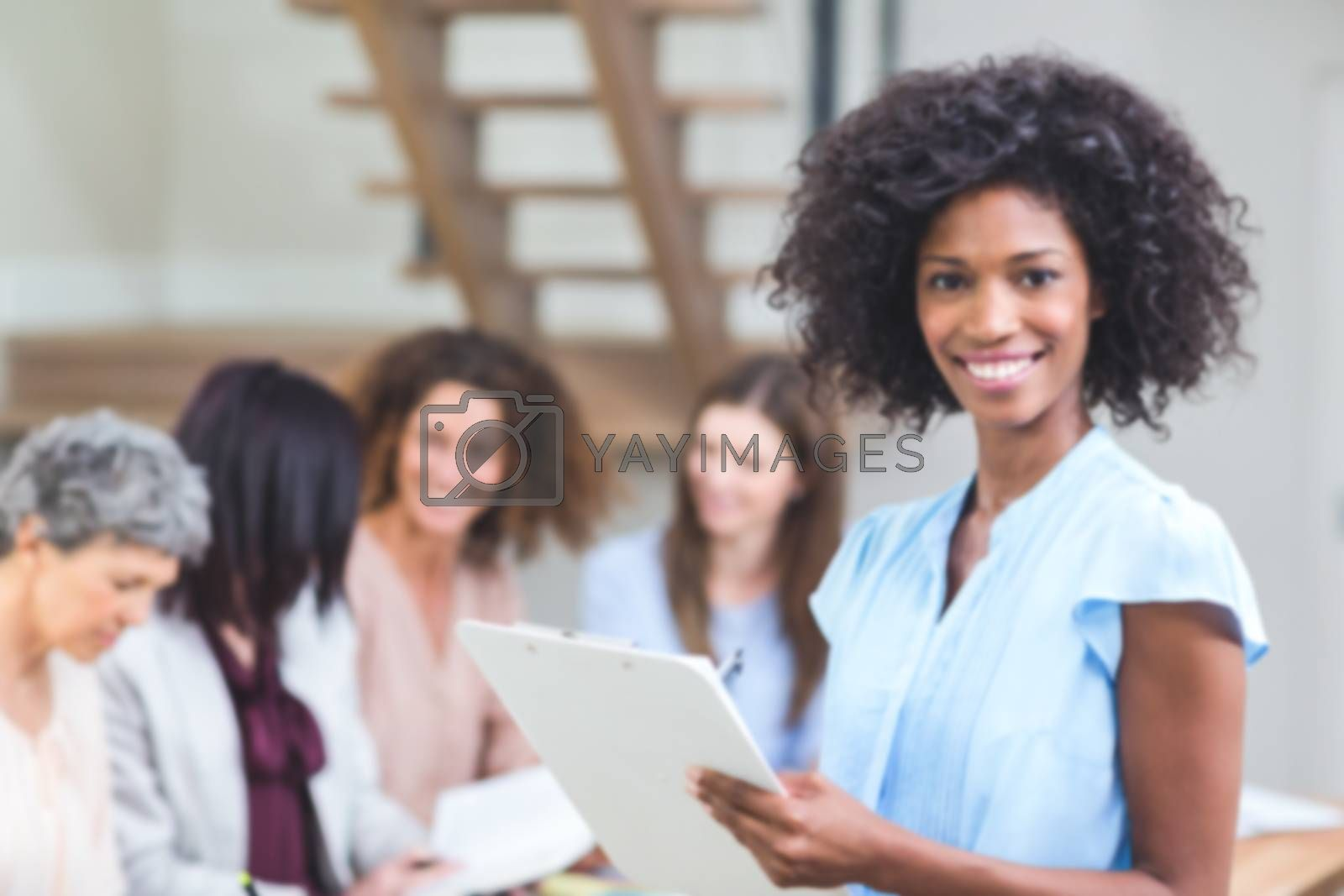 Portrait of happy businesswoman with clipboard In office